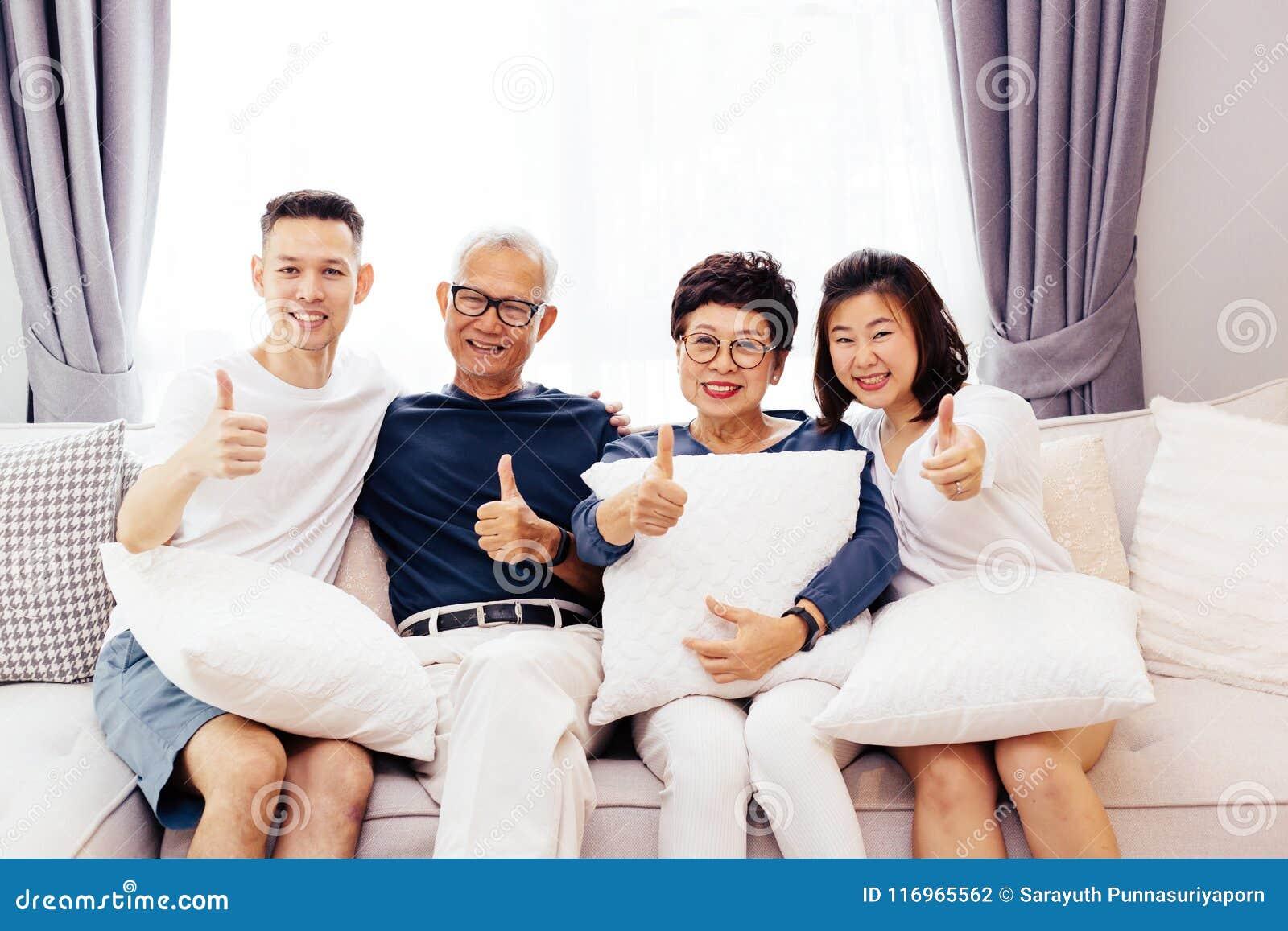 Den asiatiska familjen med vuxna barn och pensionären uppfostrar att ge upp tummar och att koppla av på en soffa hemma tillsamman