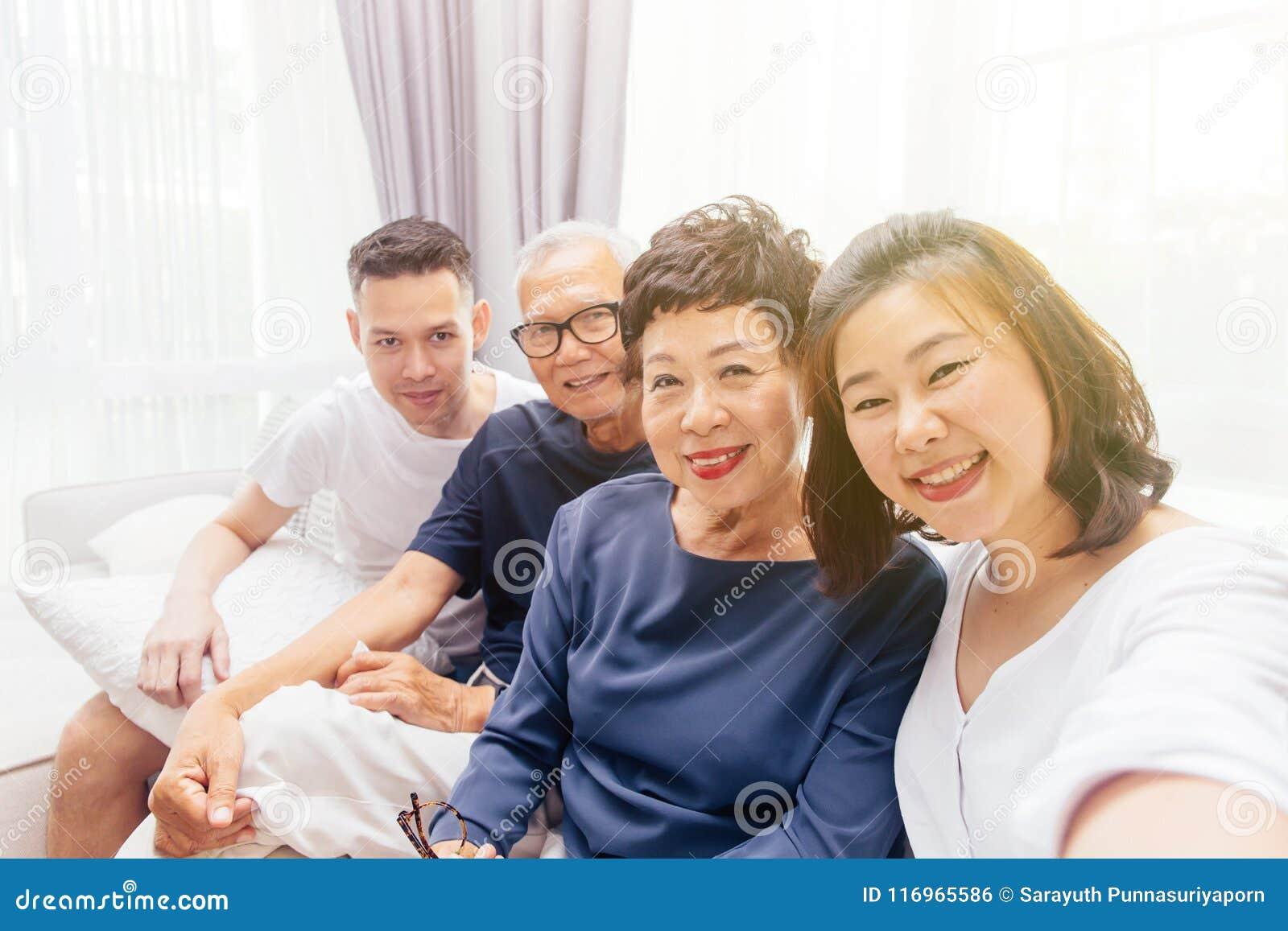 Den asiatiska familjen med vuxna barn och pensionären uppfostrar att ta selfie och att sitta på en soffa hemma Lycklig och avslap