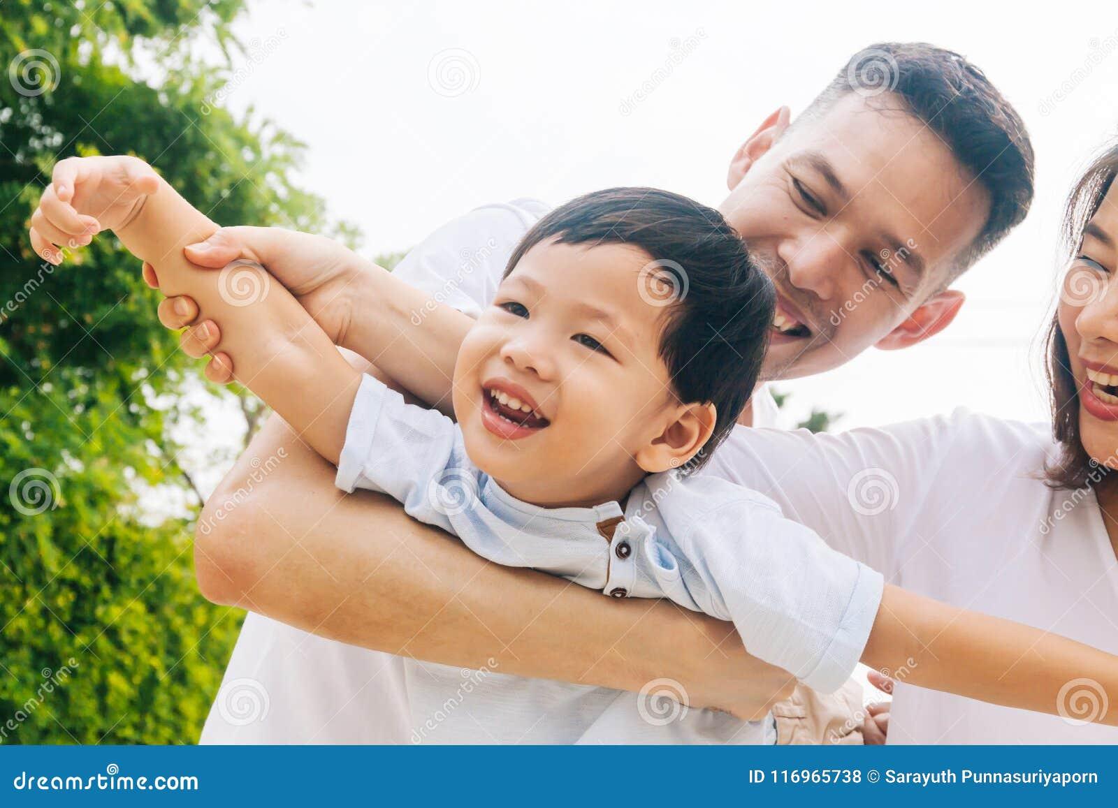 Den asiatiska familjen som har roligt och bär ett barn parkerar offentligt