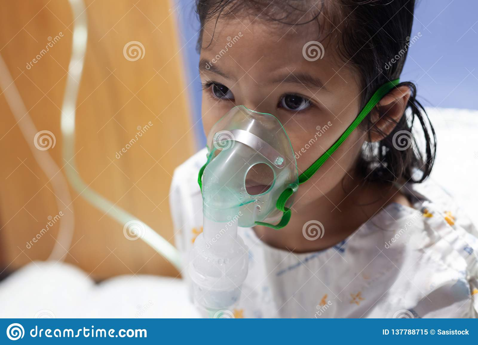 Den asiatiska flickan har astma, eller lunginflammationsjukdom- och behovsnebulizationen får förbi inhalatormaskeringen på hennes