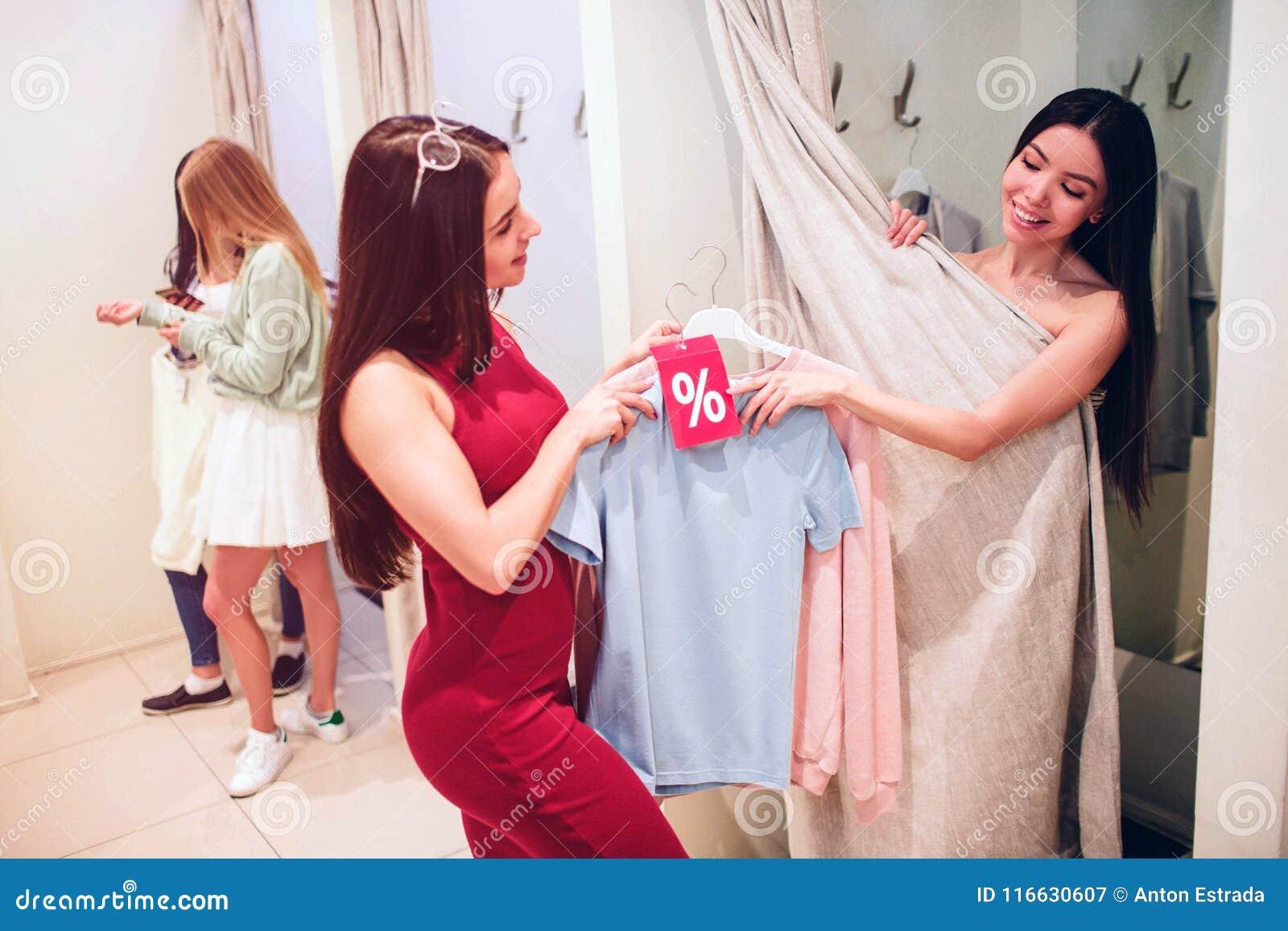Den asiatiska flickan tar blått, och rosa färger avfärdar skjortor från flicka i röd klänning Hon önskar att försöka dem på henne