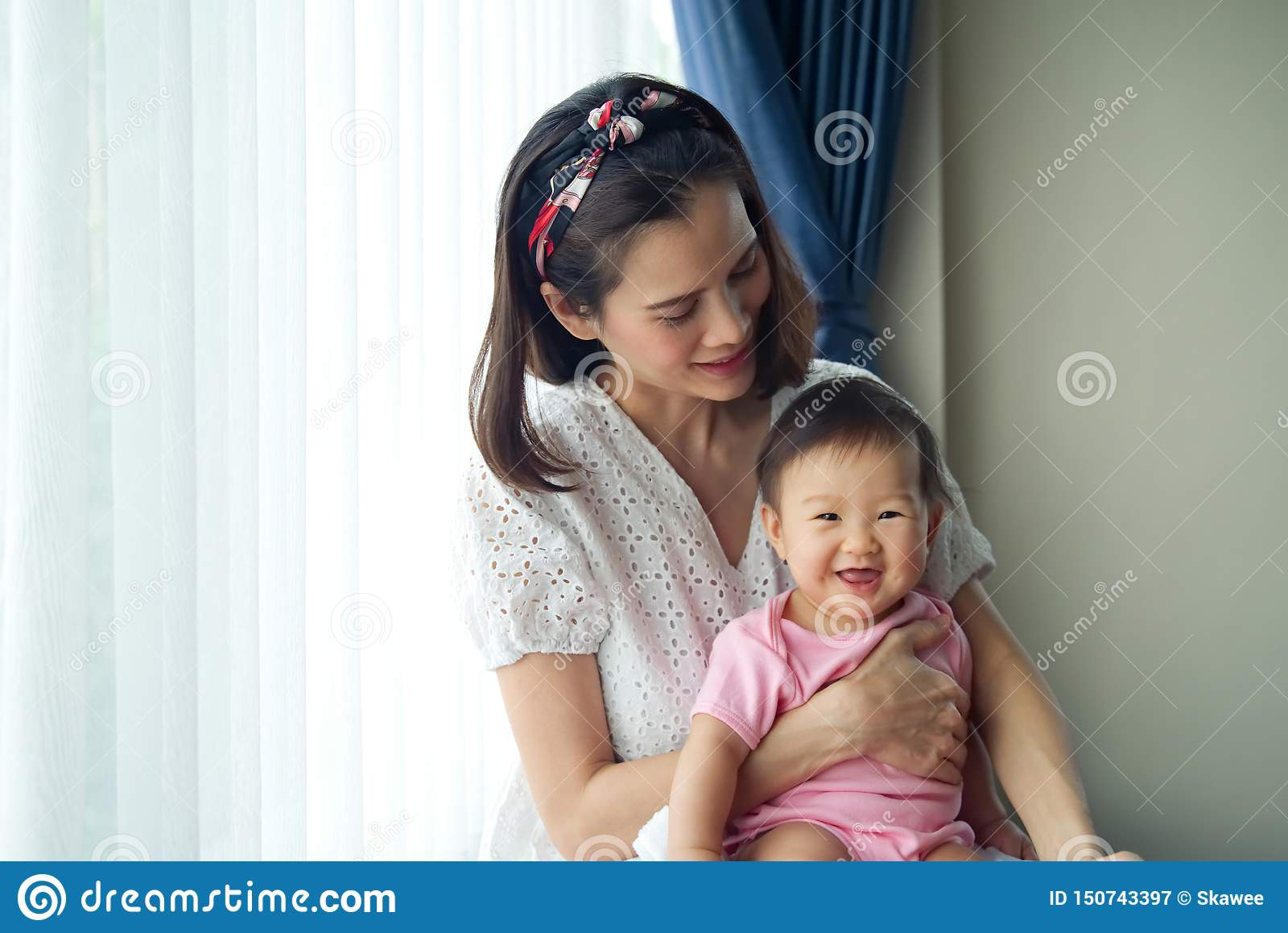 Den asiatiska härliga modern som rymmer hennes gulligt, behandla som ett barn i hennes armar som hemma sitter nära fönstret