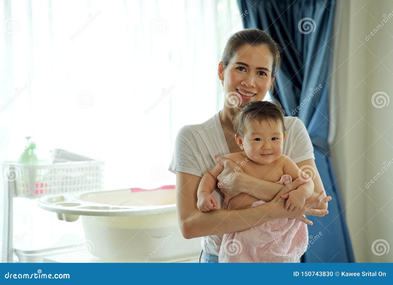 Den asiatiska härliga modern som rymmer litet gulligt, behandla som ett barn, når han har tagit ett bad
