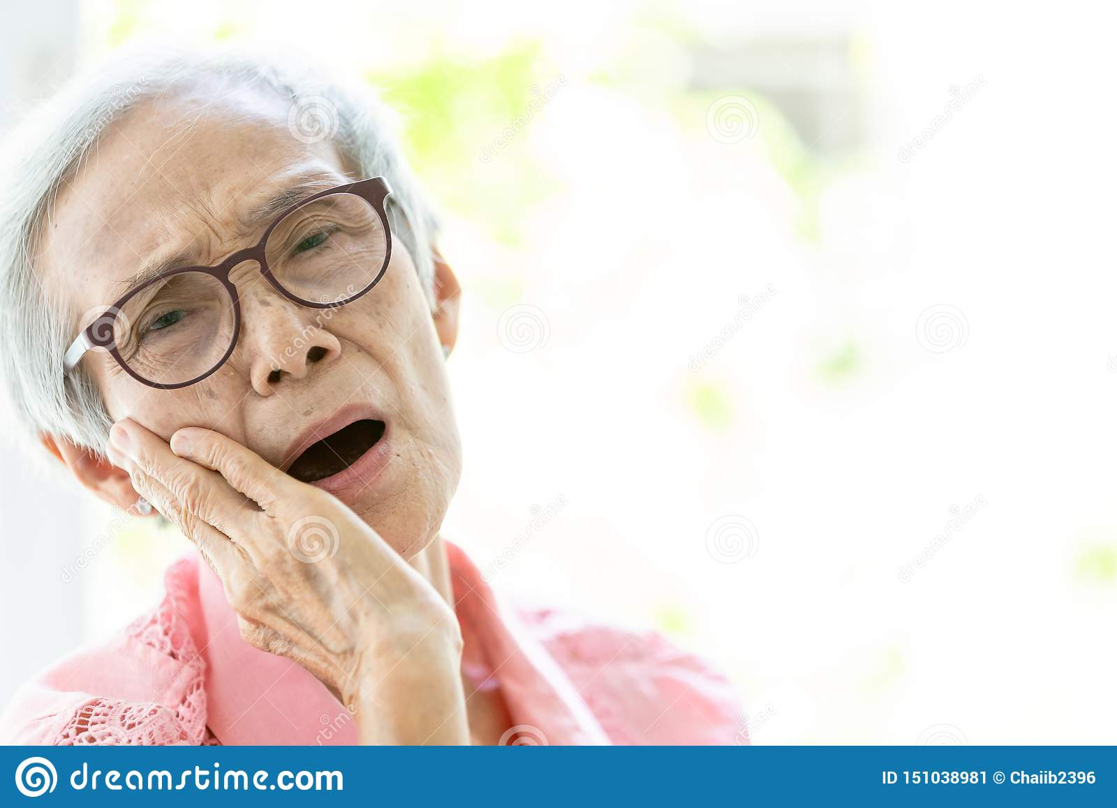 Den asiatiska höga kvinnan som lider från tandvärk, tandförfall, känsla smärtar, kvinnligt äldre folk som rymmer hennes kind med