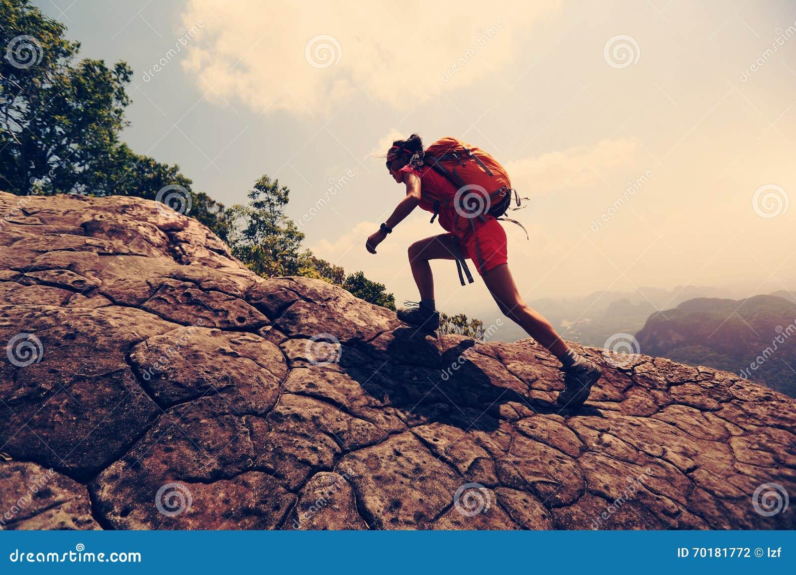 Den asiatiska kvinnafotvandrareklättringen vaggar på klippan för bergmaximumet