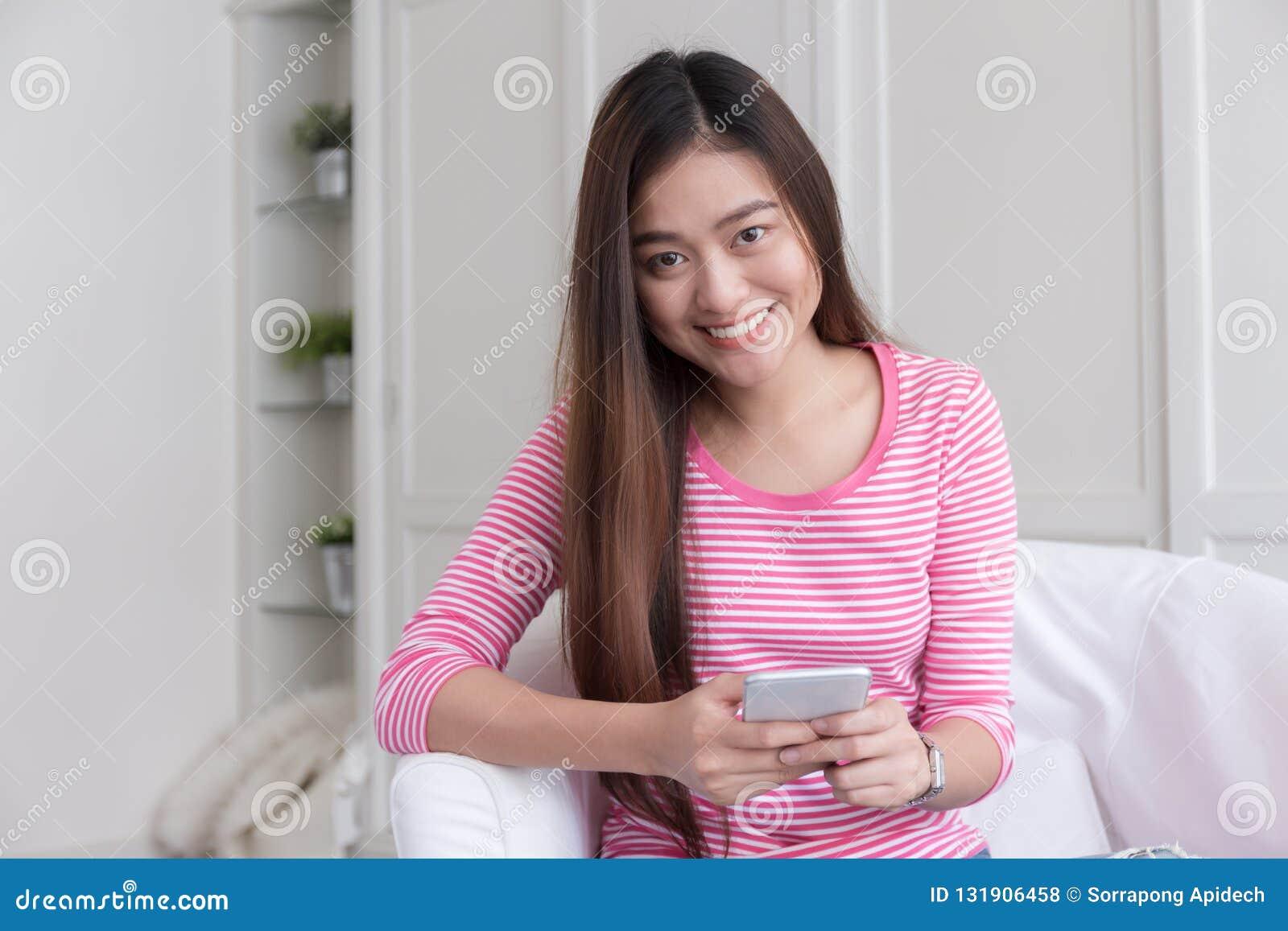 Den asiatiska kvinnan är le och genom att använda smartphonen på suddig backgroun