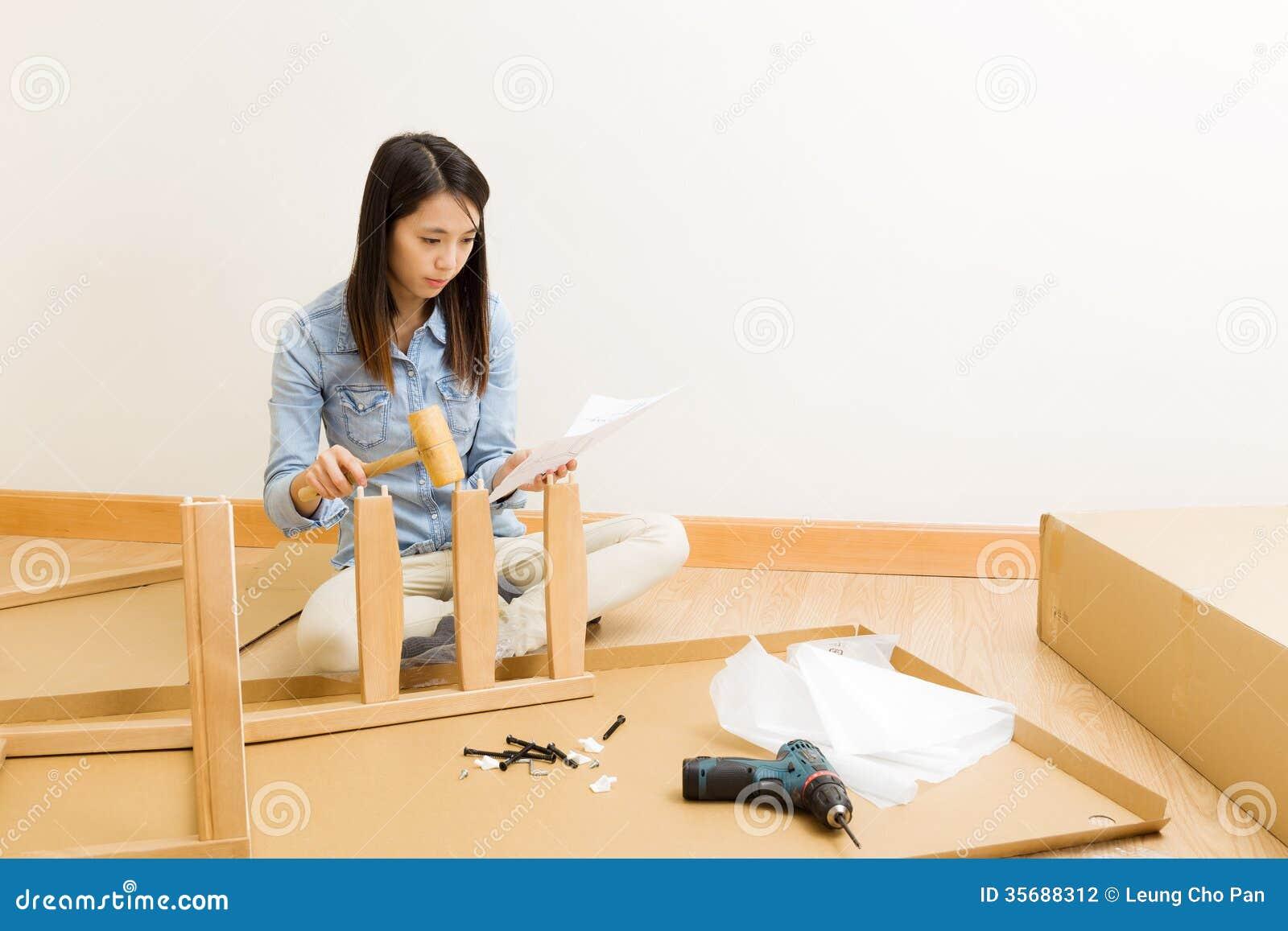 Den asiatiska kvinnan följer anvisning för monterande stol