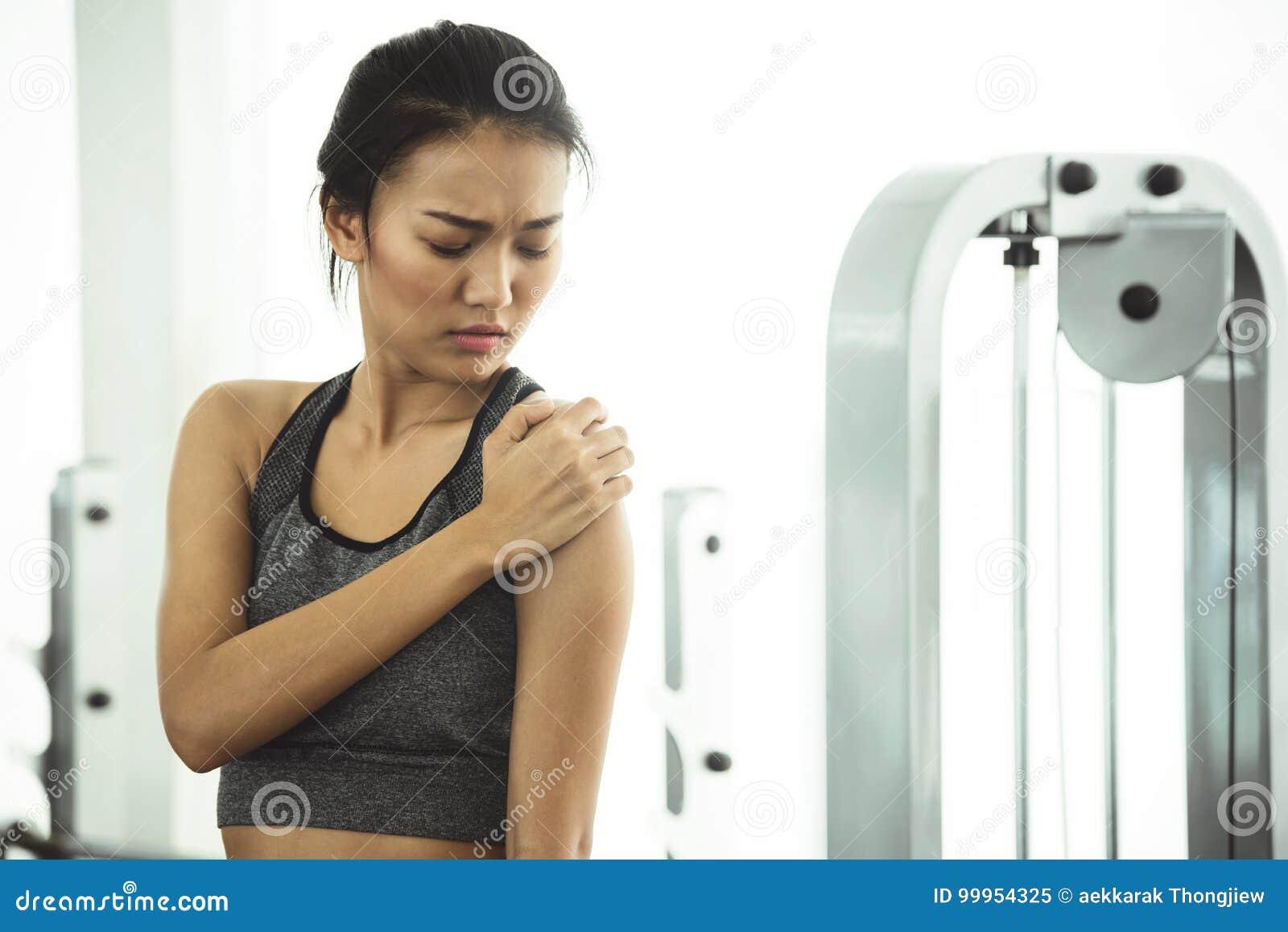 Den asiatiska kvinnan i sportswearen som har skuldran, smärtar