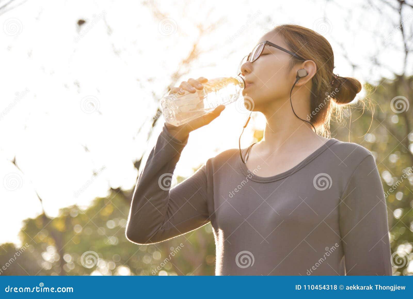 Den asiatiska kvinnlign vilar och dricksvatten
