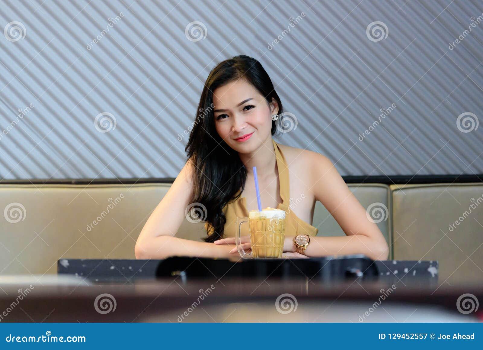 Den asiatiska nätta flickan har att koppla av med kaffe på kaffekaférestaurangen