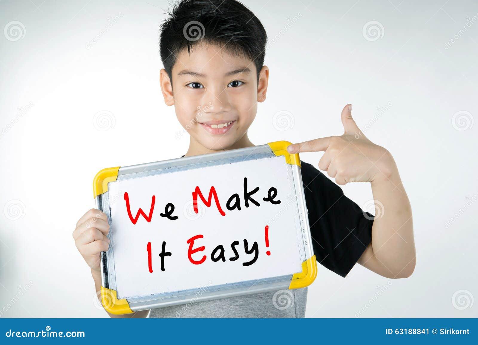 Den asiatiska pojken med GÖR VI IT LÄTT! meddelande på det vita brädet