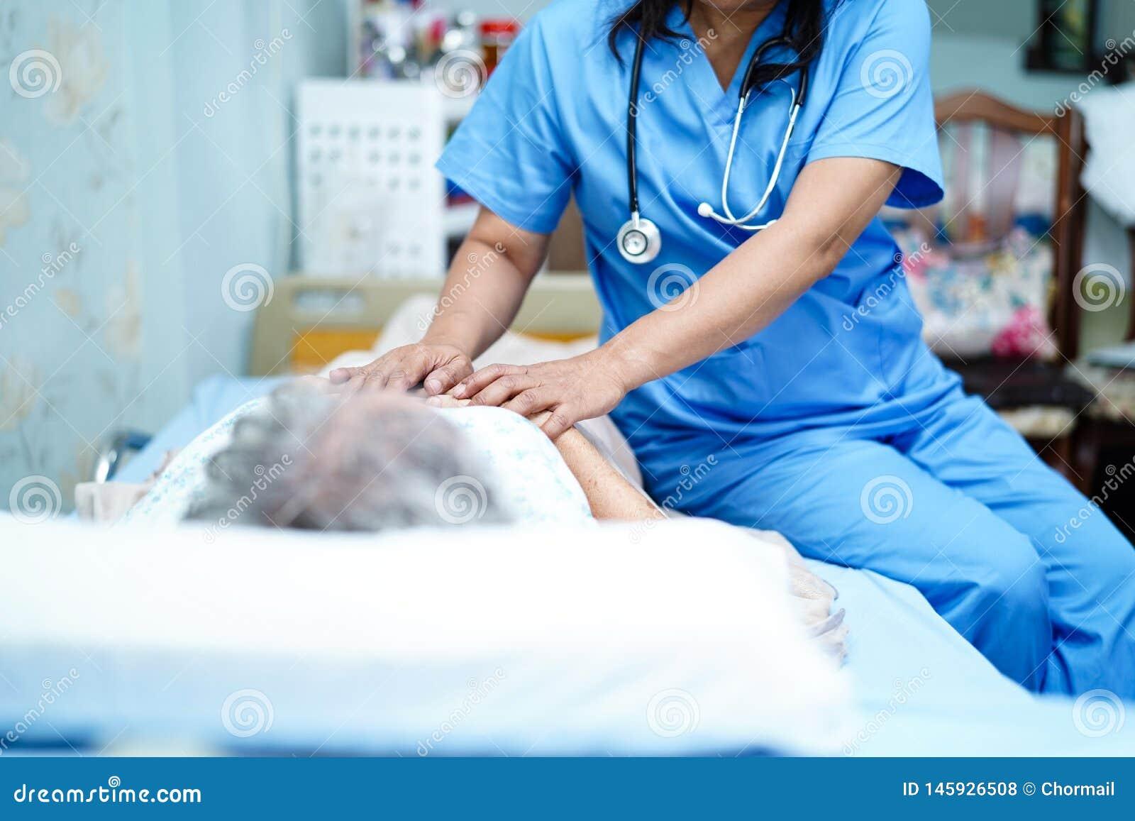 Den asiatiska sjuksk?terskafysioterapeutdoktorn att att bry sig, hj?lpa och st?tta den h?ga eller ?ldre kvinnapatienten f?r den g