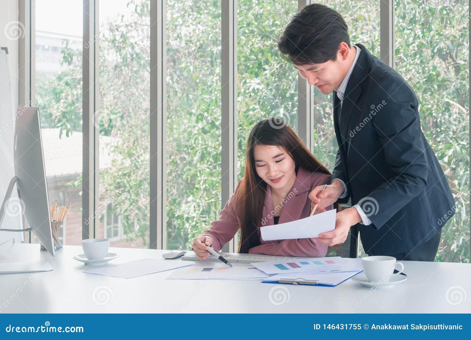 Den asiatiska stiliga affärsmannen i den marinblåa dräktställningen som förklarar jobbdetaljer till den härliga affärskvinnan för