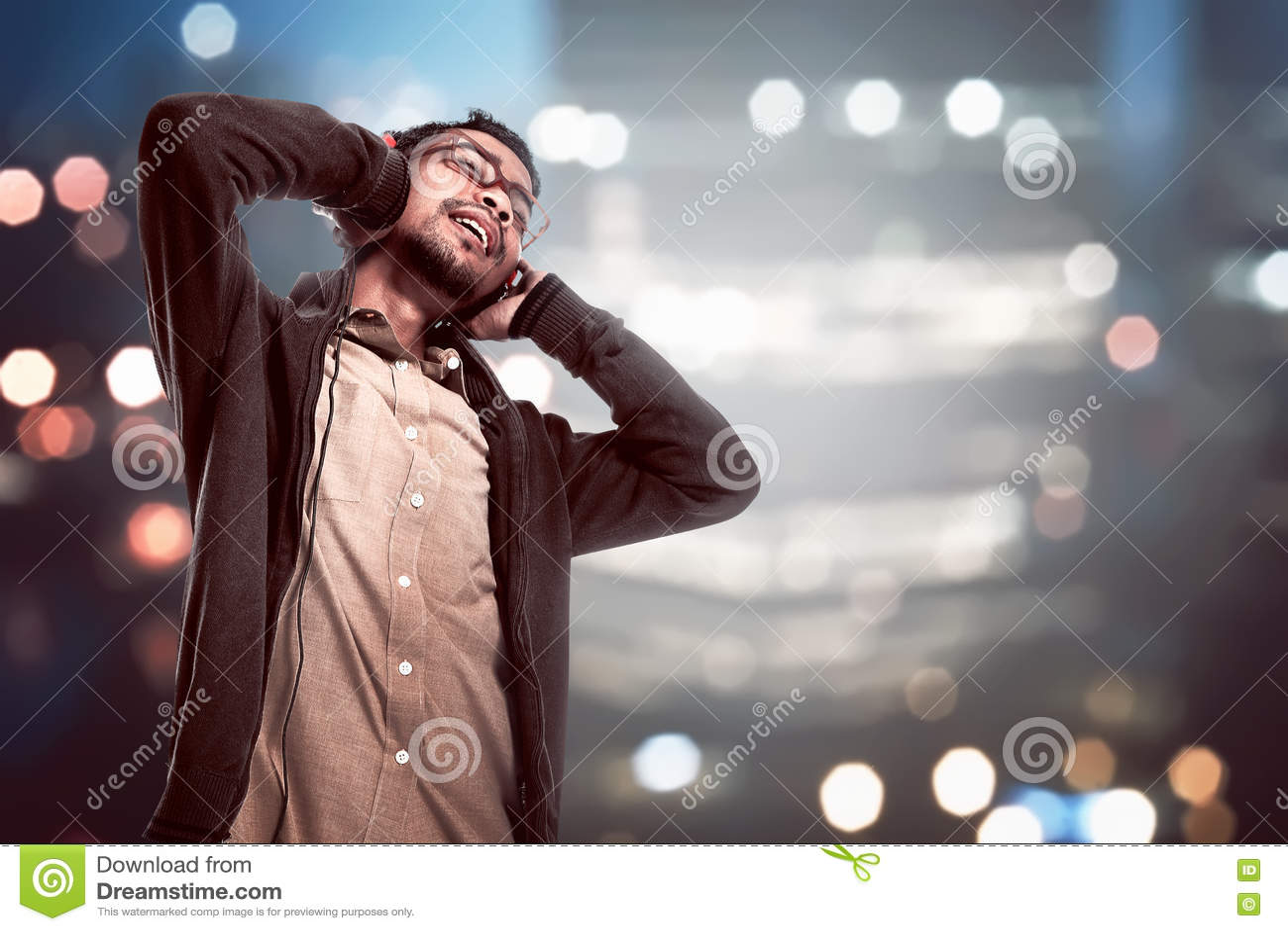 Den asiatiska unga mannen lyssnar till musik via headphonen
