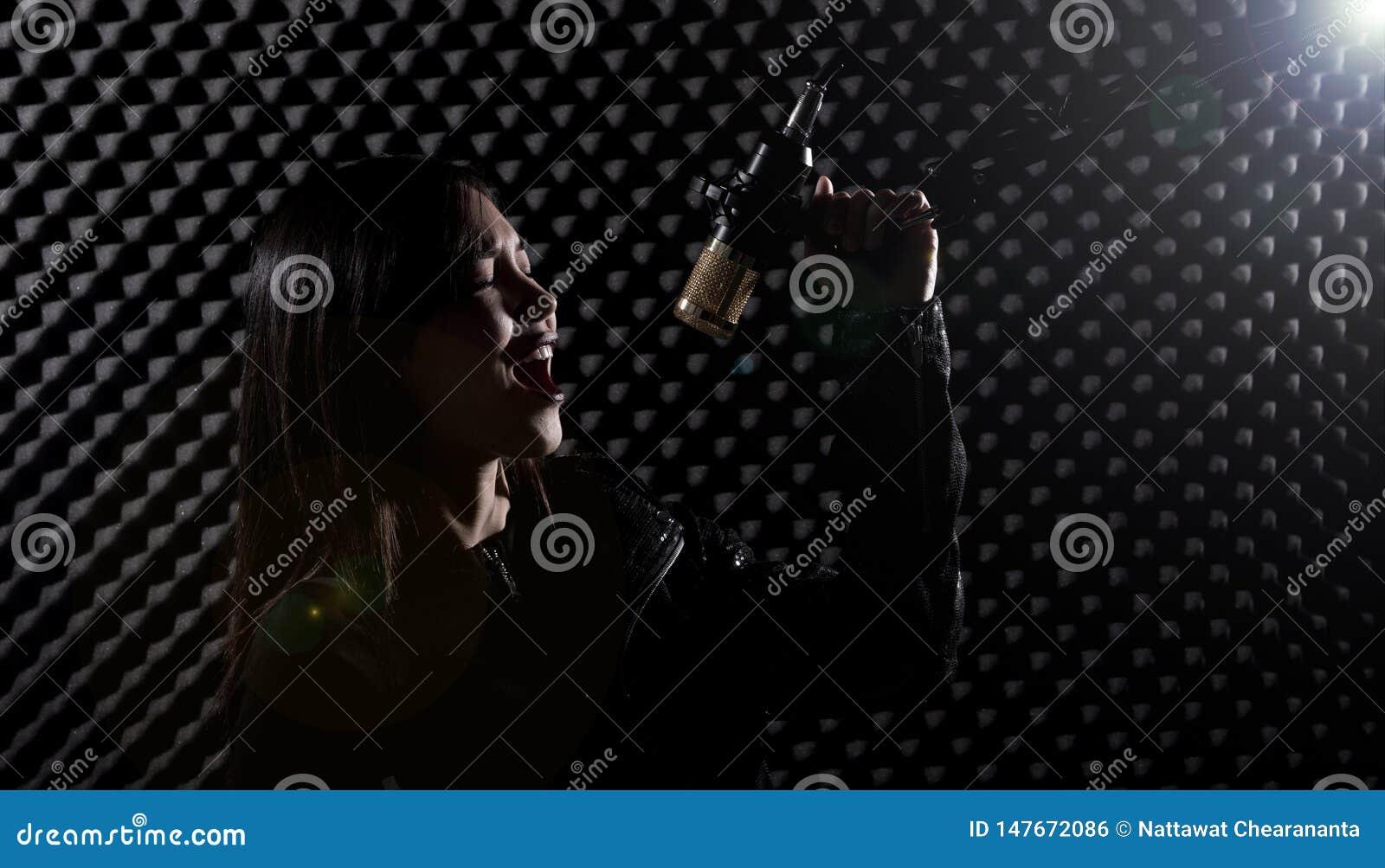 Den asiatiska vuxna kvinnan sjunger en s?ng driver h?gt ljudet