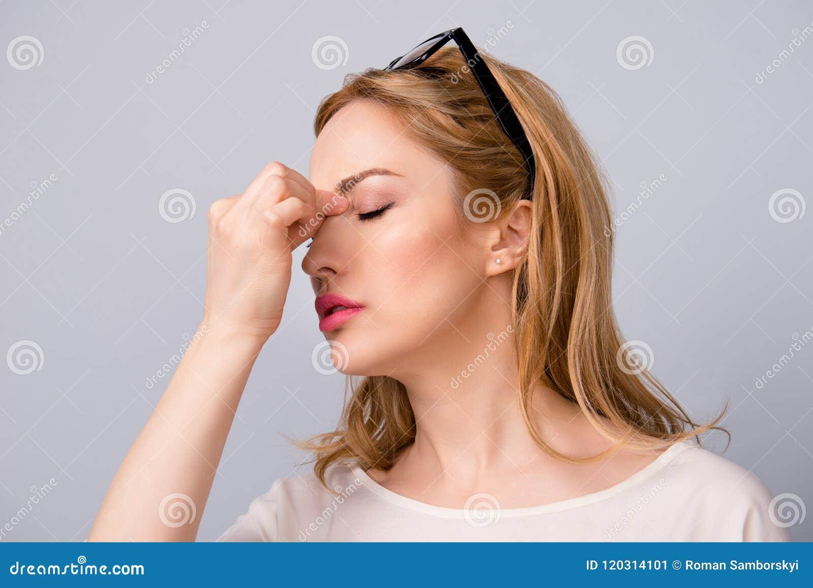 Den attraktiva affärskvinnan tröttade på arbetslidande från huvudvärk som isolerades på grått bakgrundslidande från touvhing näsa
