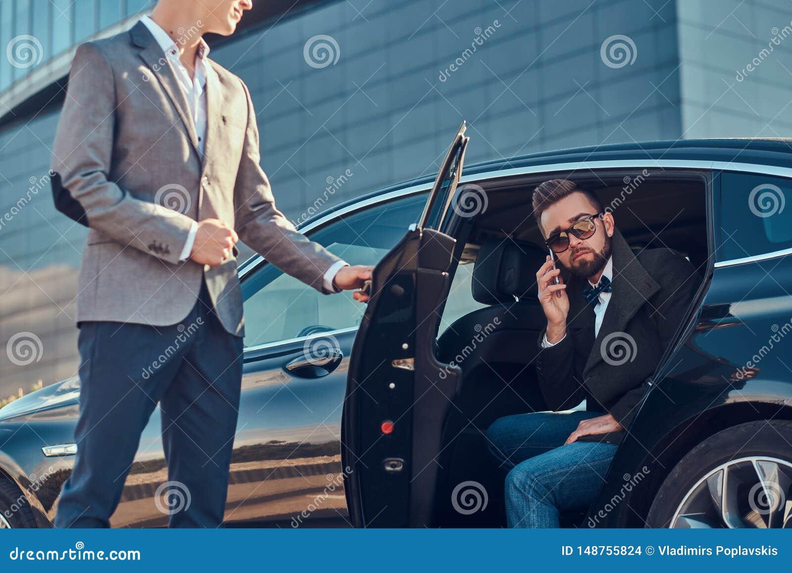 Den attraktiva ansade mannen i solglasögon talar vid smartphonen och sitter i bilen, medan hans assistent är den öppnande dörren