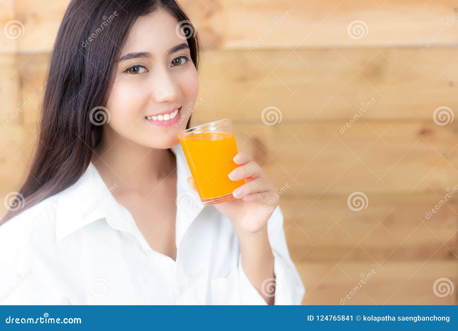 Den attraktiva härliga asiatiska kvinnan dricker orange fruktsaft berlock