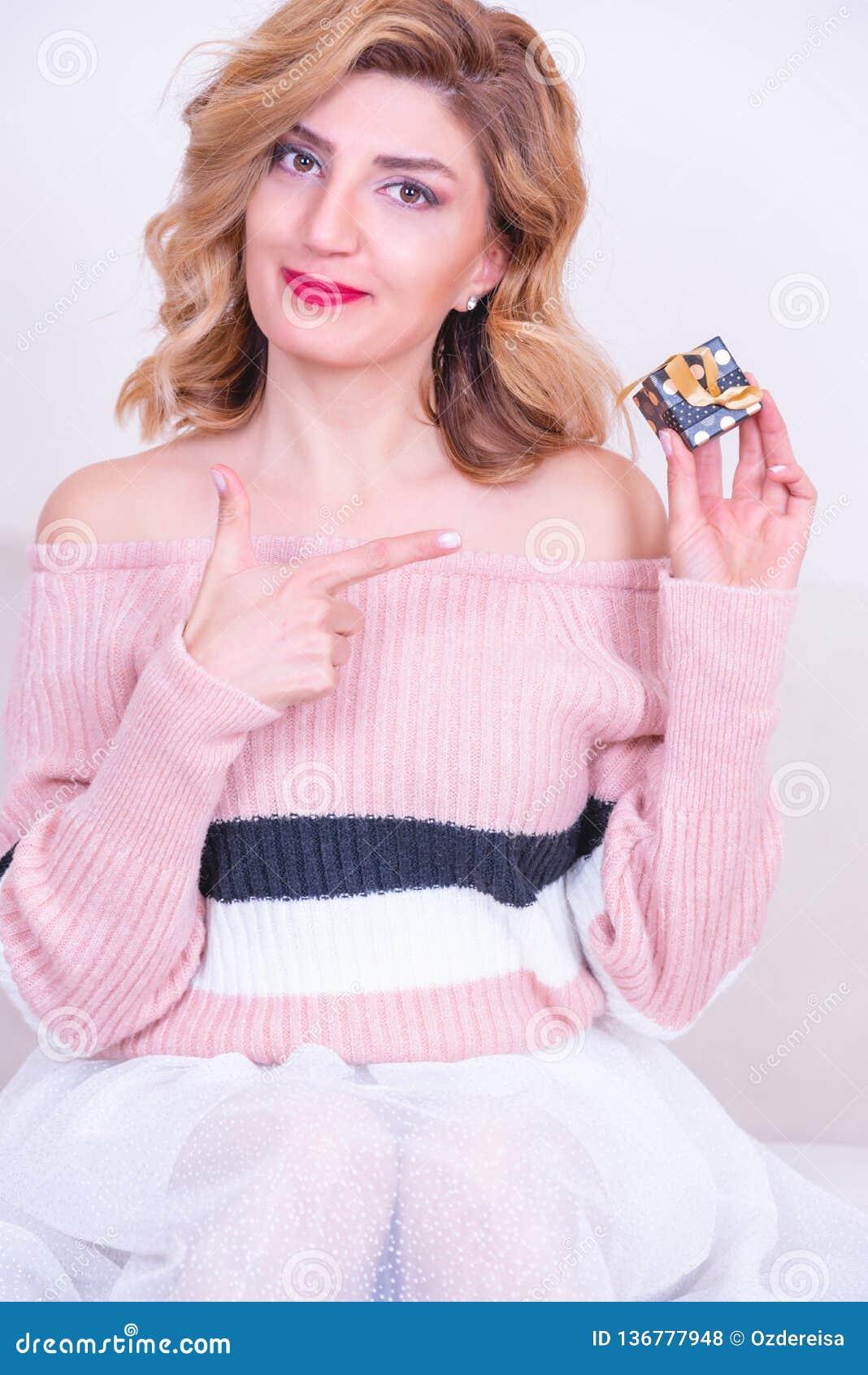 Den attraktiva härliga modellkvinnan rymmer den lilla gåvaasken