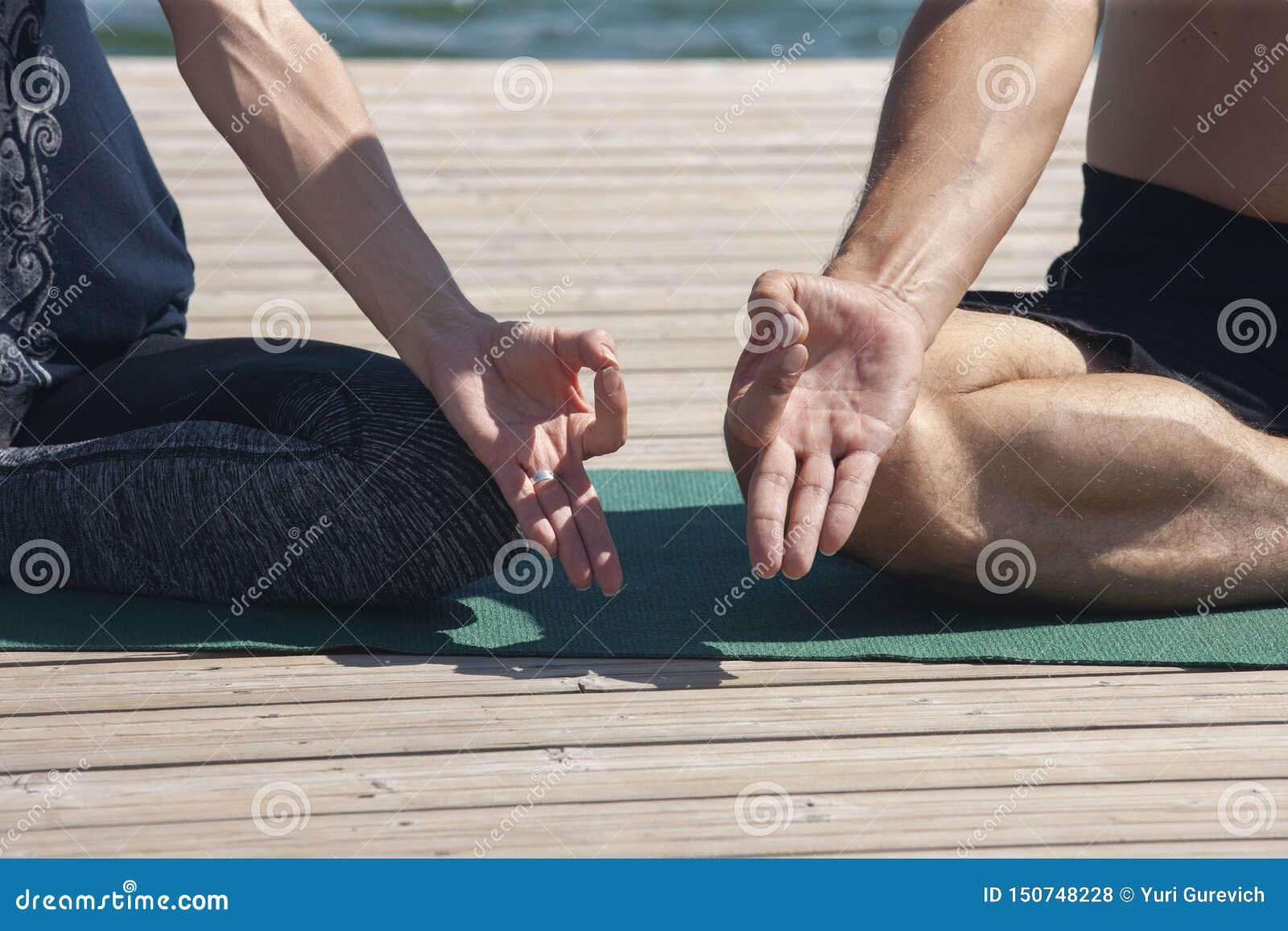 Den attraktiva mannen och kvinnlig praktiserande yoga i lotusblomma poserar slut upp händer Ett ungt par som gör yoga för att med