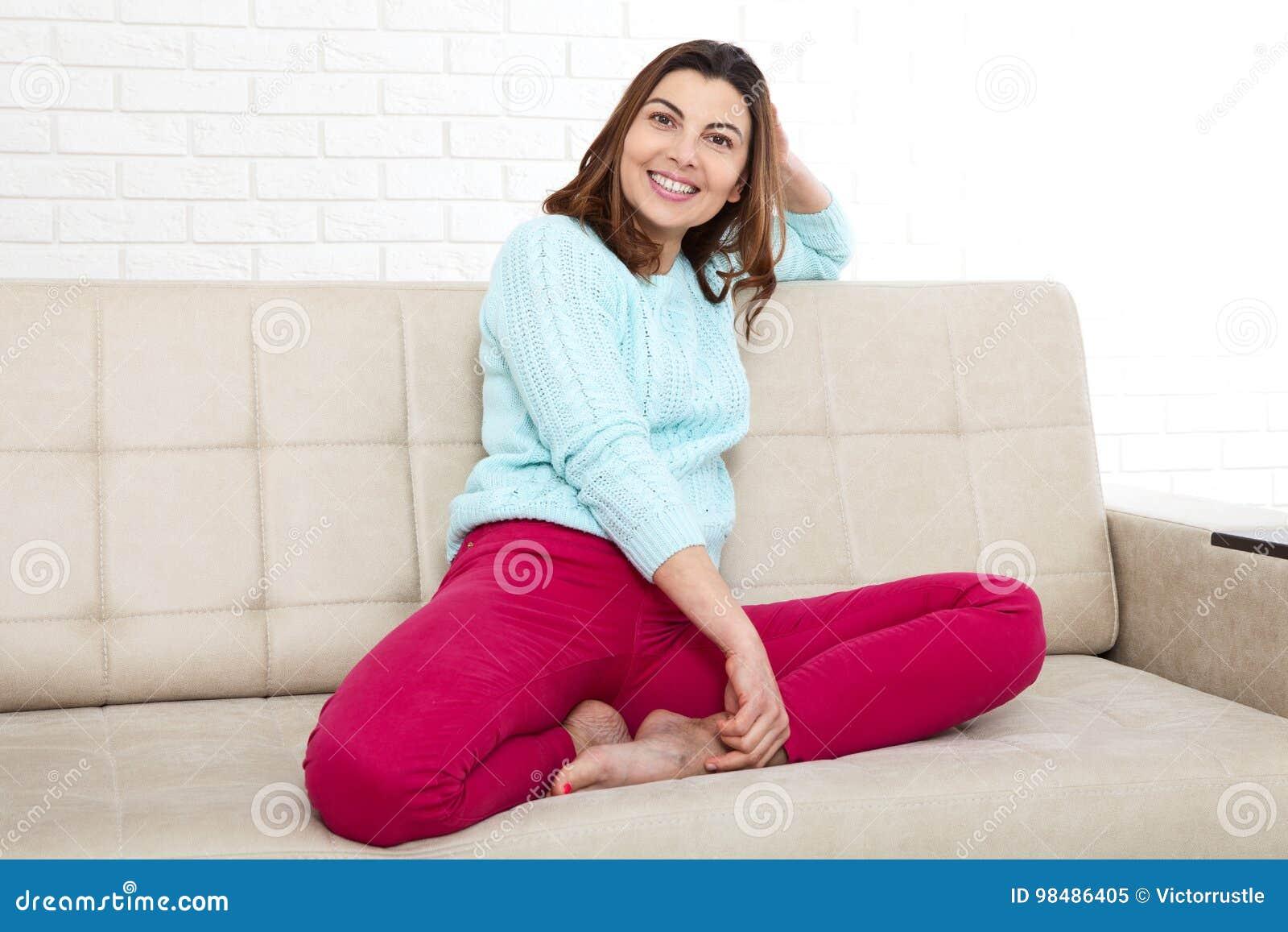 Den attraktiva mitt åldrades kvinnan som in camera ser koppla av hemma Det härliga framsidaslutet upp