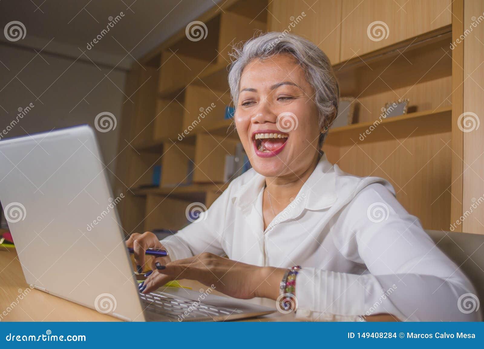 Den attraktiva och lyckliga lyckade mitt ?ldrades den asiatiska kvinnan f?r aff?ren som arbetar p? att le f?r skrivbord f?r b?rba
