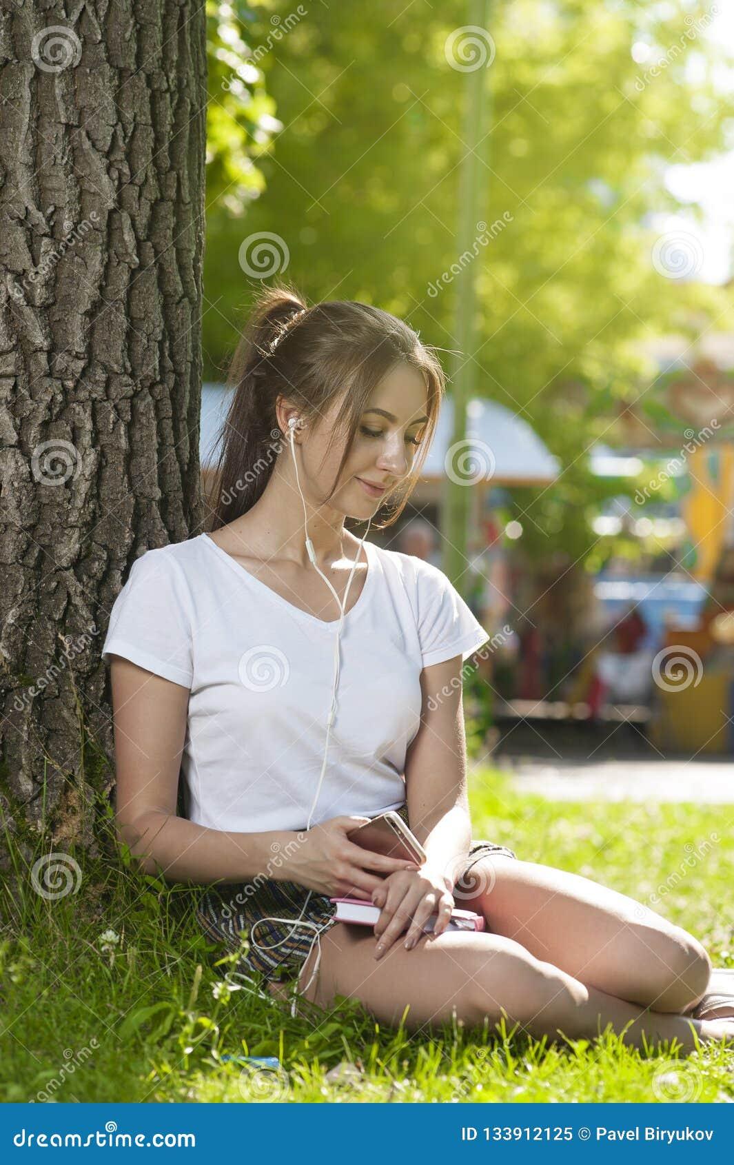 Den attraktiva studentflickan parkerar in det fria