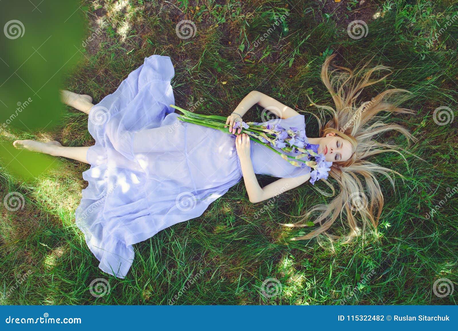 Den attraktiva unga flickan med blont hår och naturligt smink som luktar den blåa purpurfärgade irins, blommar att ligga på gräs