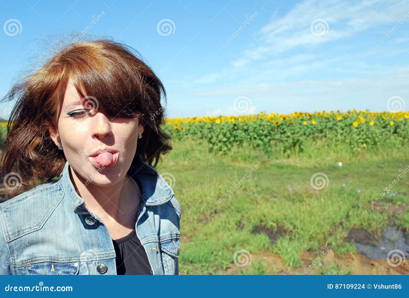 Den attraktiva unga flickan som är lycklig sätter ut tungan mot bakgrunden av fältet av solrosor