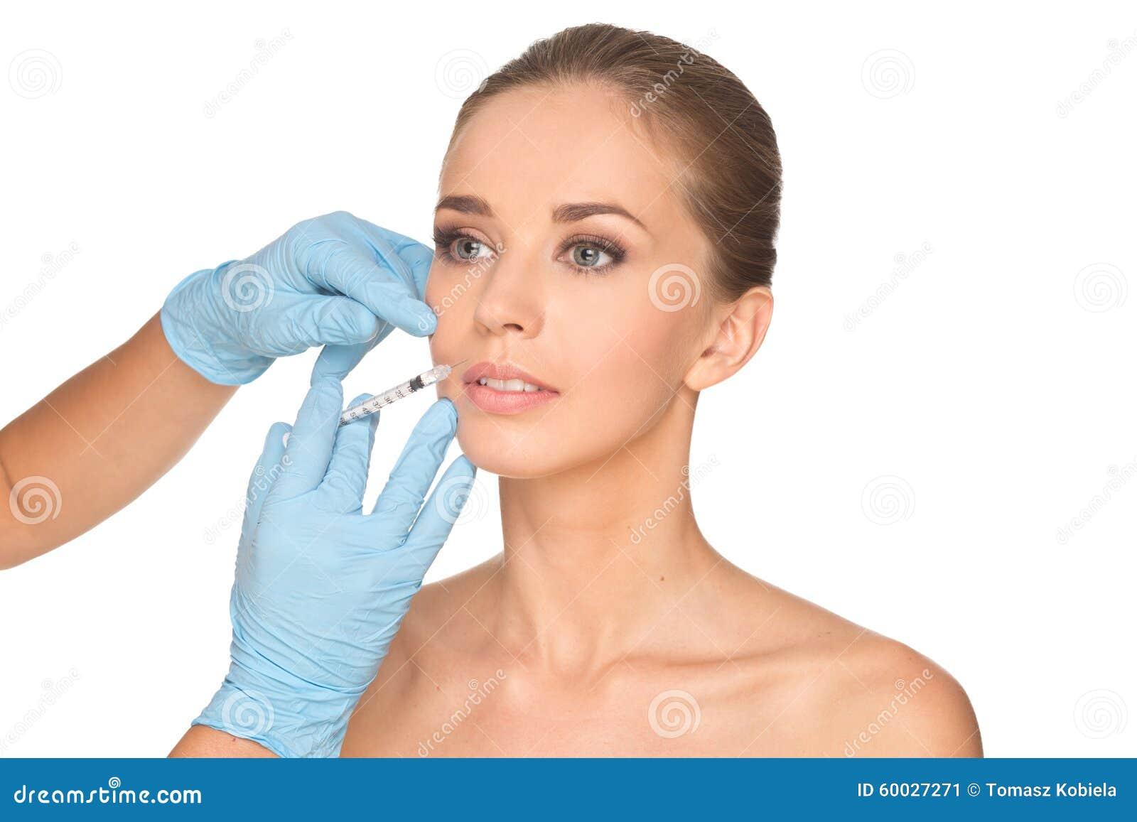 Den attraktiva unga kvinnan får den kosmetiska injektionen av botox