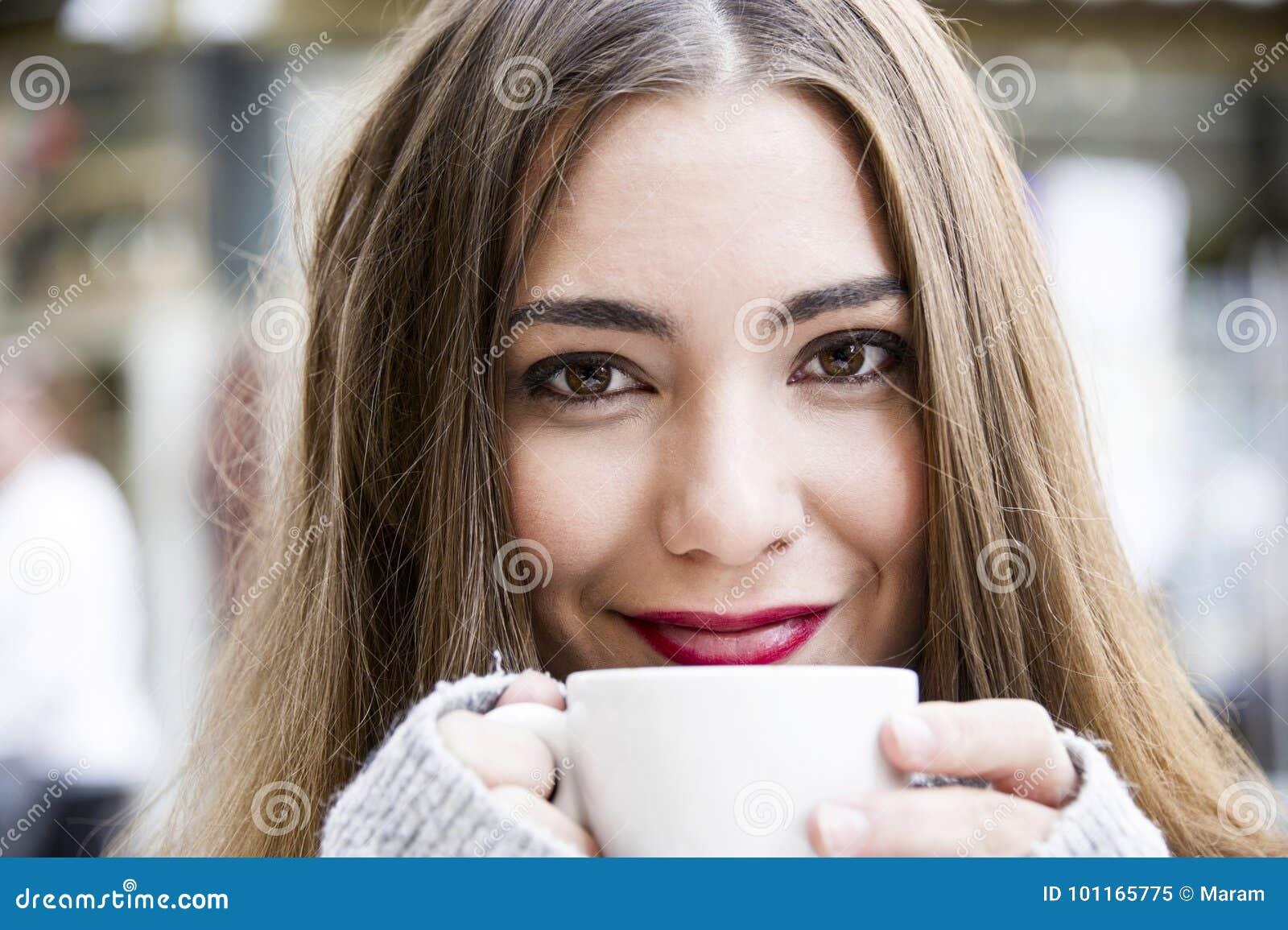 Den attraktiva unga kvinnan har ett kaffe på en gata med bakgrund för gataliv i hösttid