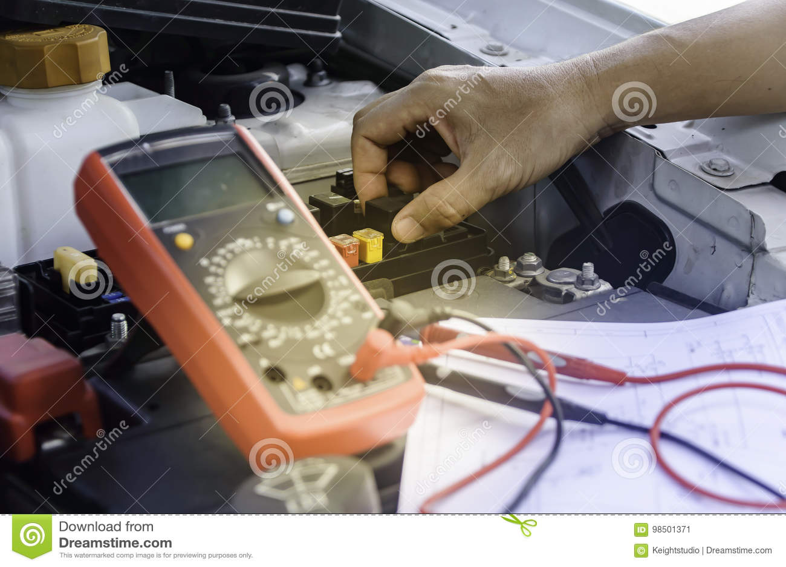 Den auto mekanikern använder en multimetervoltmeter