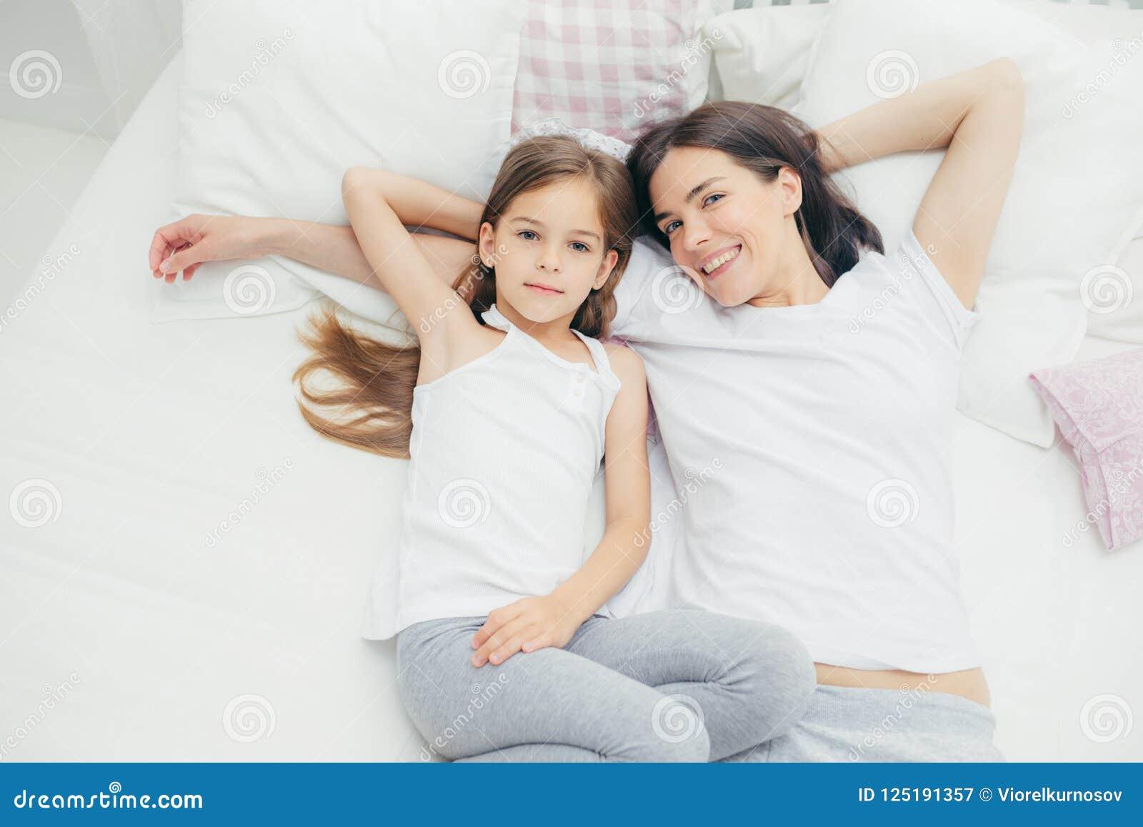 Den bästa sikten av att älska den unga modern med angenäma leendelögner nära hennes lilla dotter som går att ha sömn, tycker om l