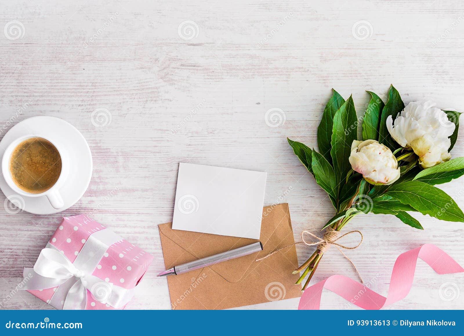 Den bästa sikten av den tomma anmärkningen, det kraft kuvertet, kaffekoppen och pionen blommar över vit wood lantlig bakgrund kop
