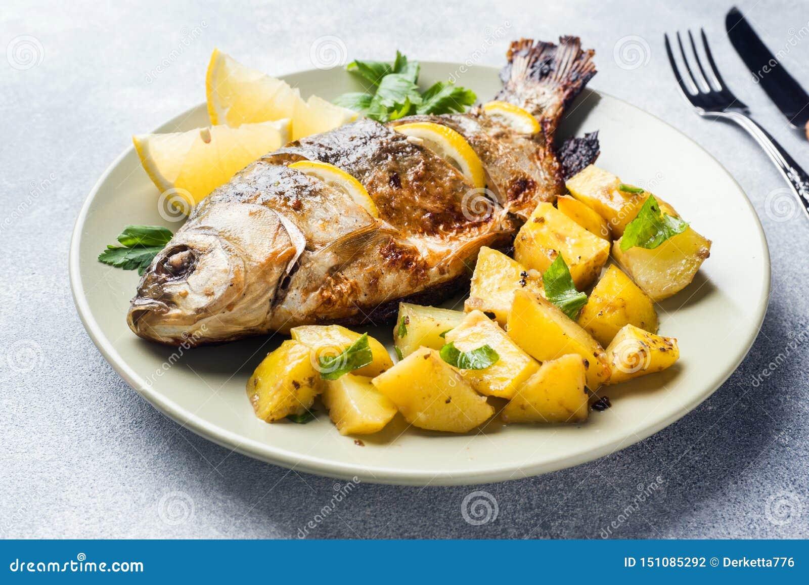 Den bakade fisken kverulerar med citrongr?splaner och potatisar p? en platta