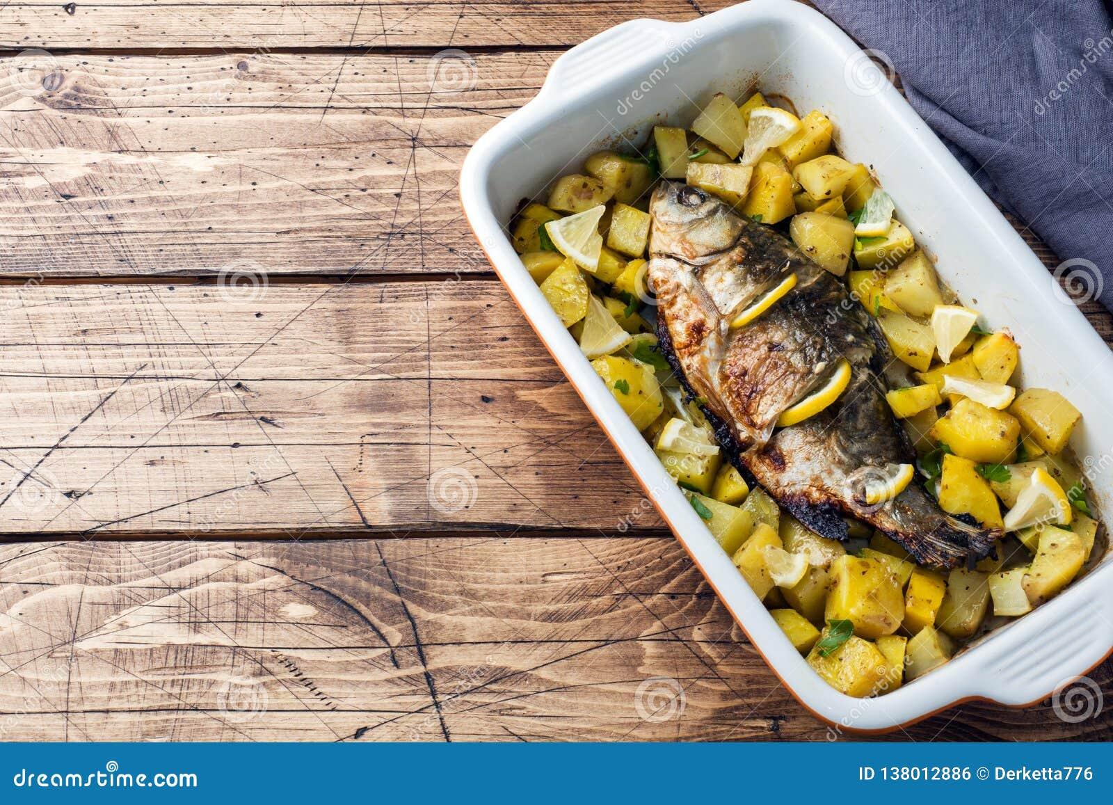 Den bakade fisken kverulerar med potatisar i en keramisk panna Lantlig stil kopiera avstånd