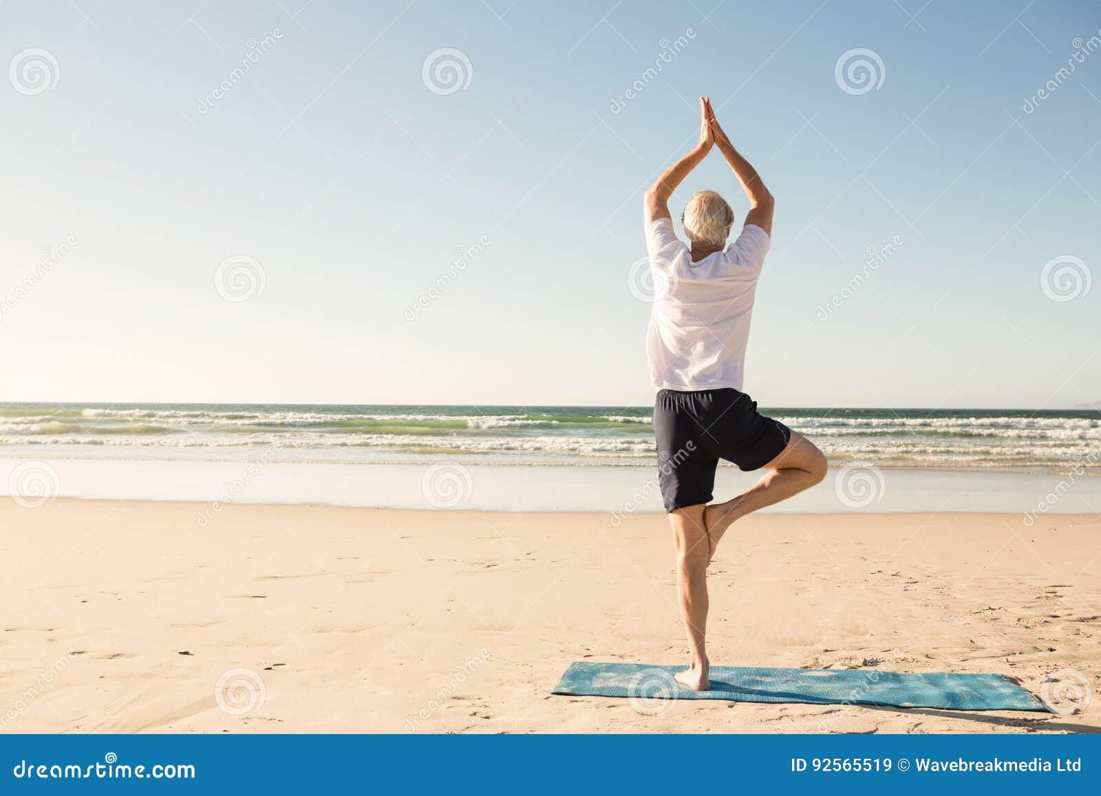 Den bakre sikten av det praktiserande trädet för den höga mannen poserar på stranden