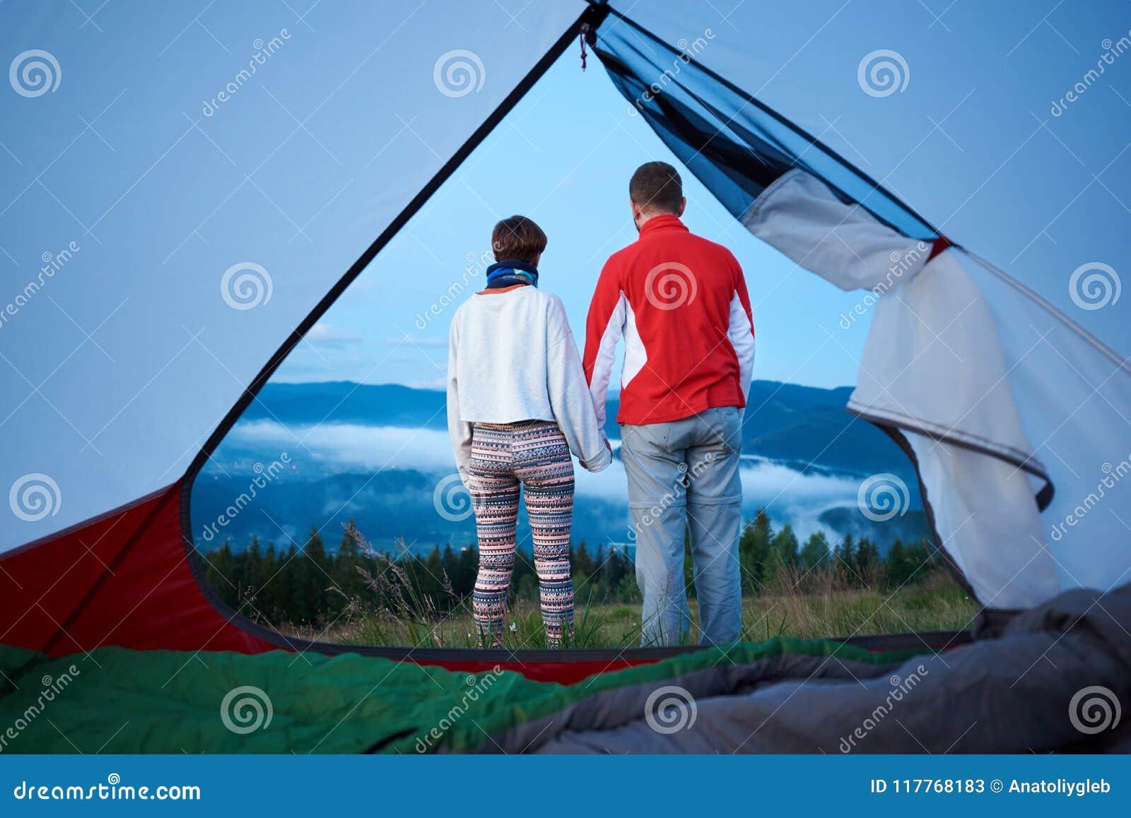 Den bakre sikten av två ungdomarsom rymmer händer, tycker om morgonlandskap av berg