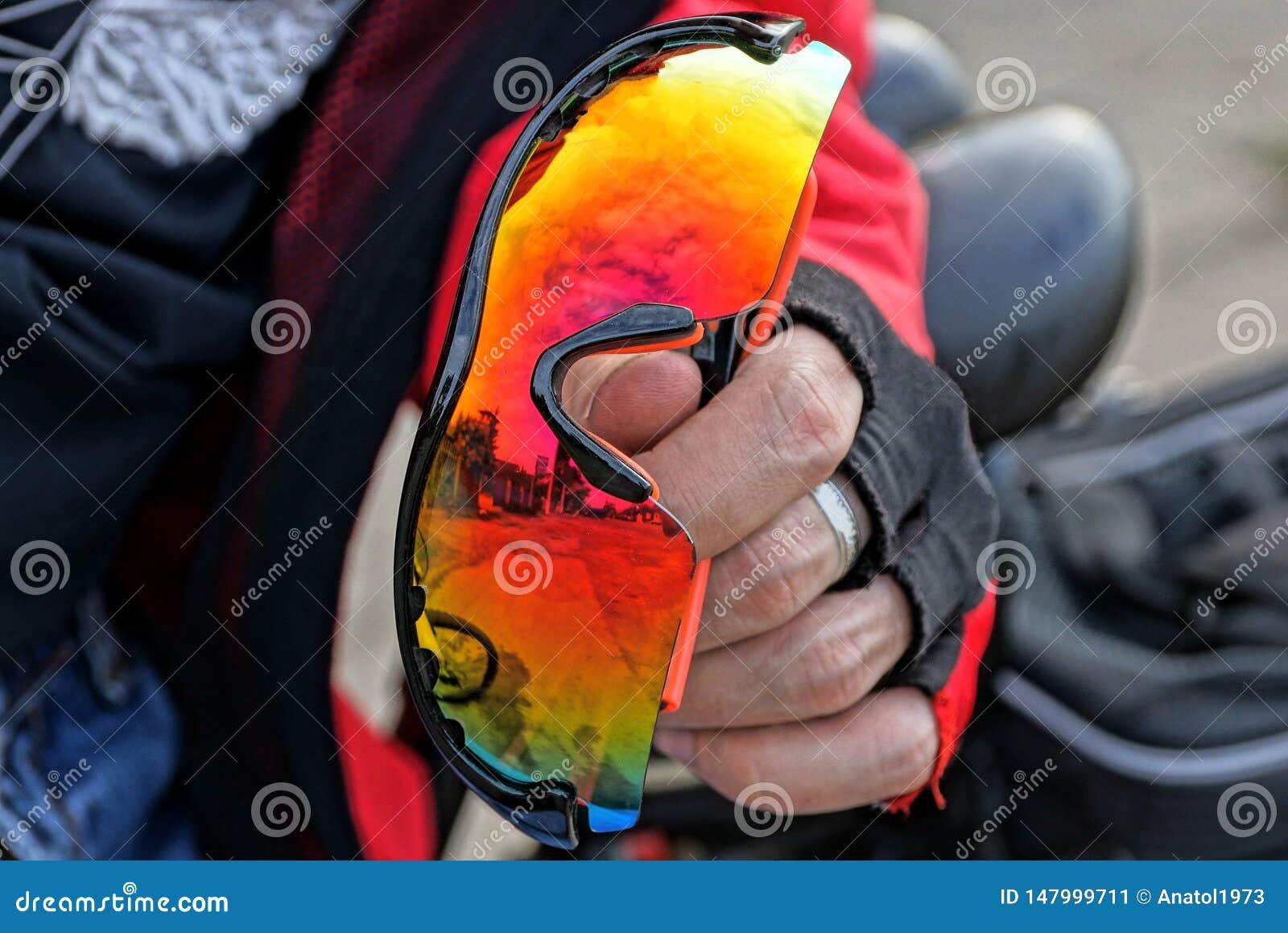 Den behandskade handen rymmer kulöra sportexponeringsglas