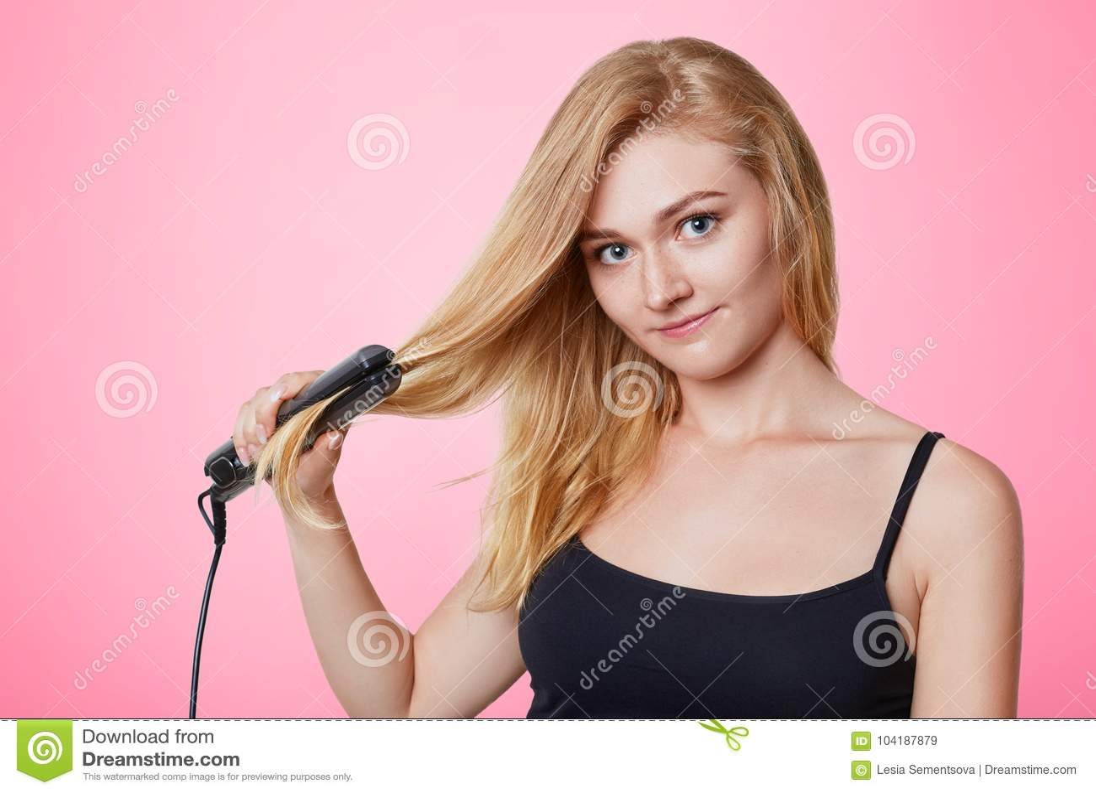 Den Beuatiful kvinnan använder hårstraighteneren för uträtning av hår, annonserar dess underbara effekt som isoleras över rosa ba