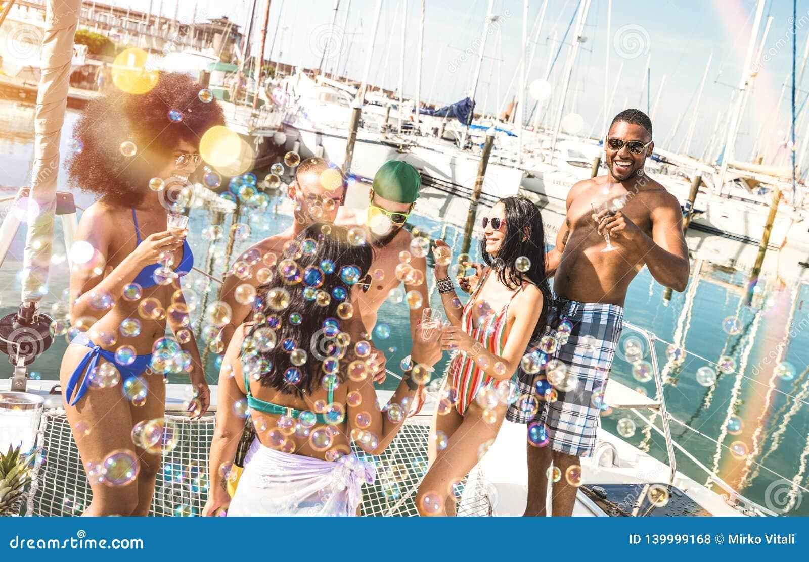 Den blandras- vängruppen som har gyckel som dricker vin på, seglar fartygpartiet - kamratskapbegrepp med ungt mång- ras- folk