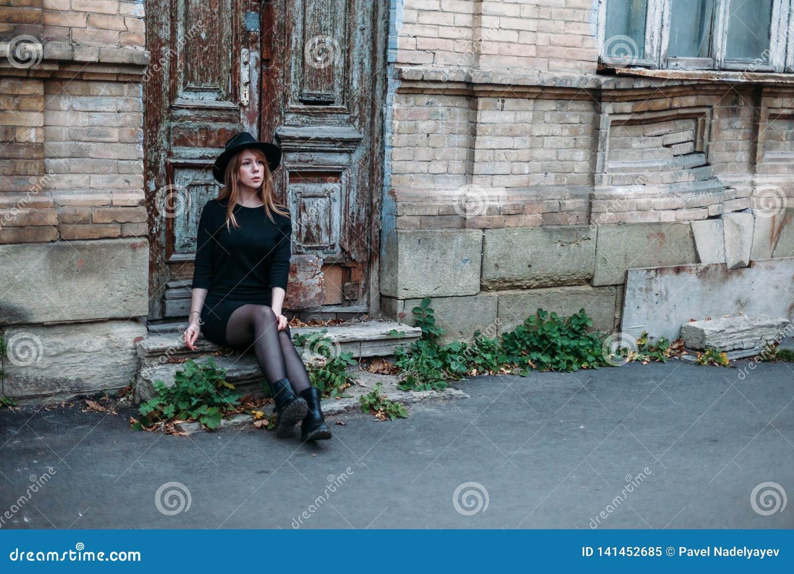 Den blonda eftertänksamma flickan med långt hår, i svart klänning i hatt, sitter på momenten på bakgrunden av gammalt trä för tap
