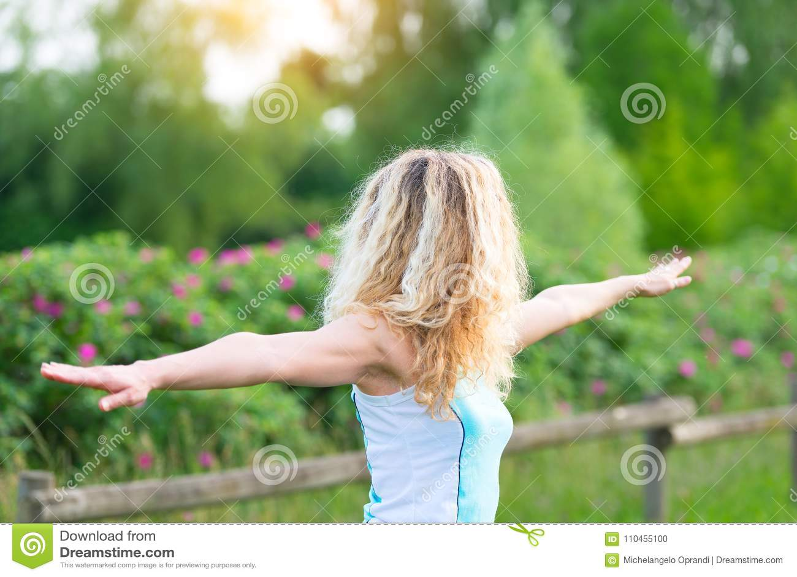 Den blonda flickan öva gymnastik i naturen