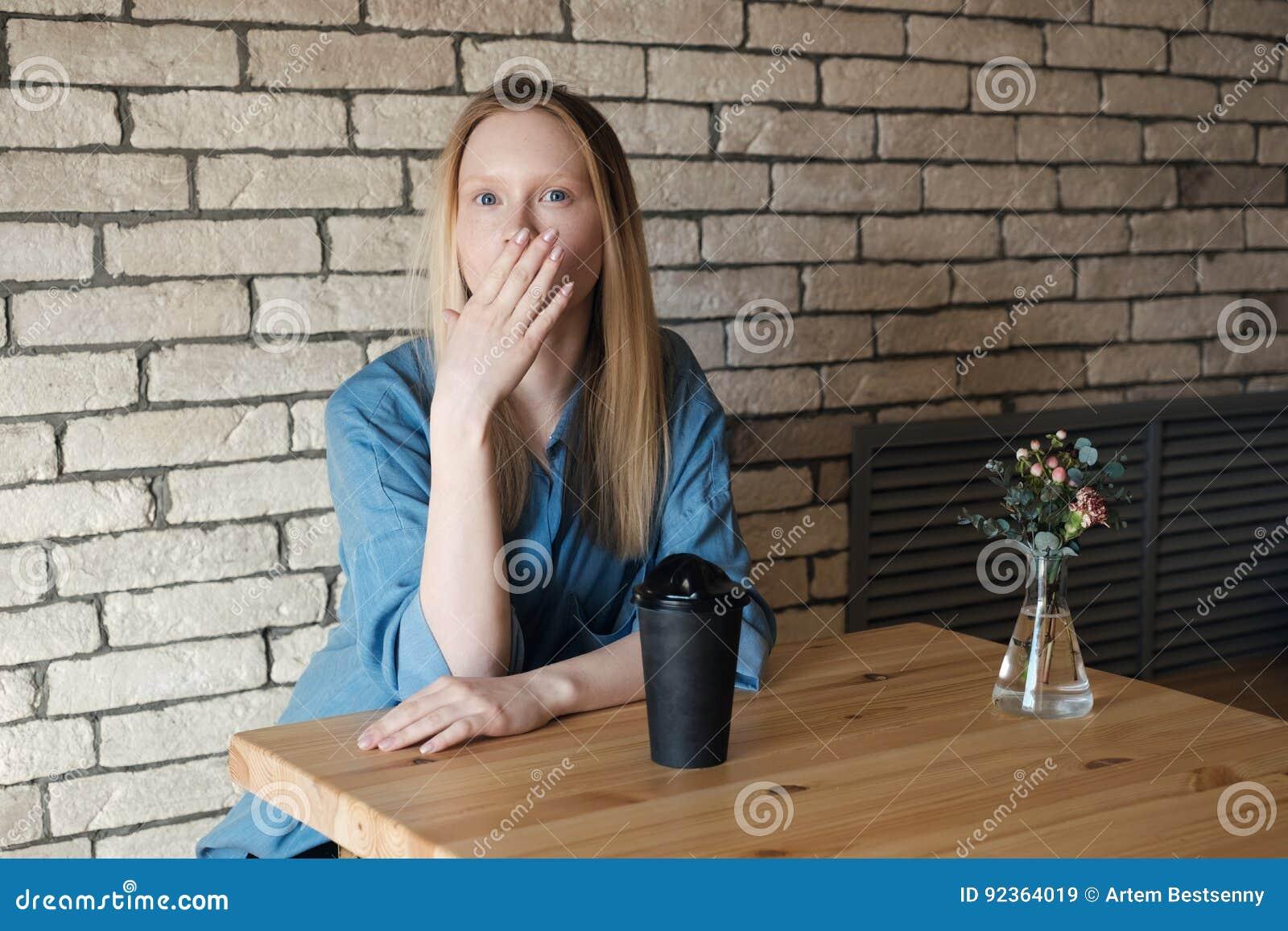 Den blonda flickan i en blå skjorta sitter på en tabell med ett exponeringsglas av kaffe som täcker henne, gömma i handflatan med