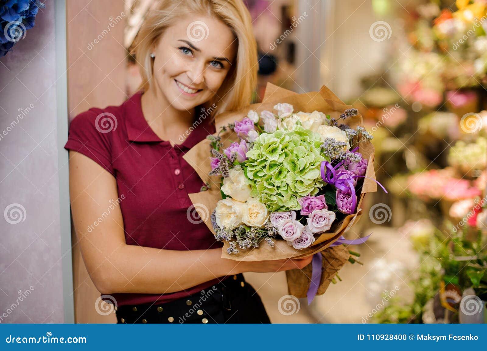 Den blonda flickan ler och rymmer i händer en stilfull bukett av rosor, vanliga hortensian och pioner