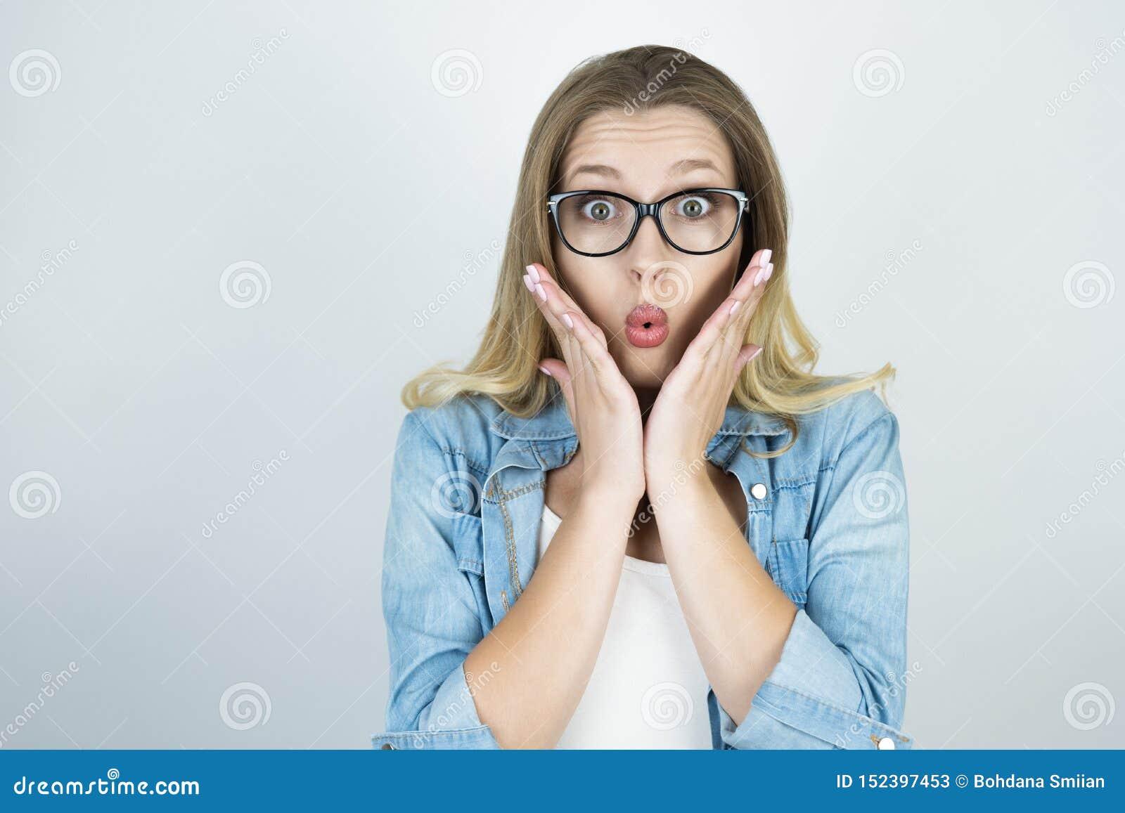 Den blonda flickan som rymmer händer förvånade nära framsida, isolerade vit bakgrund