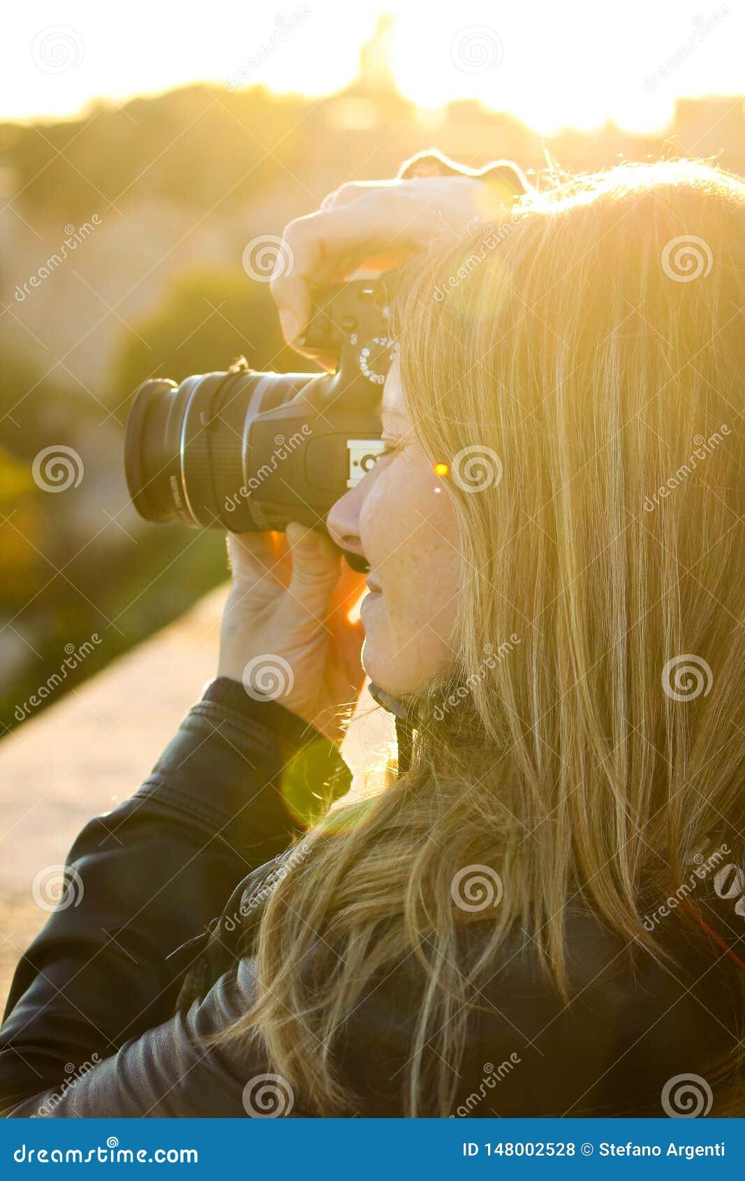 Den blonda flickan tar foto med reflex