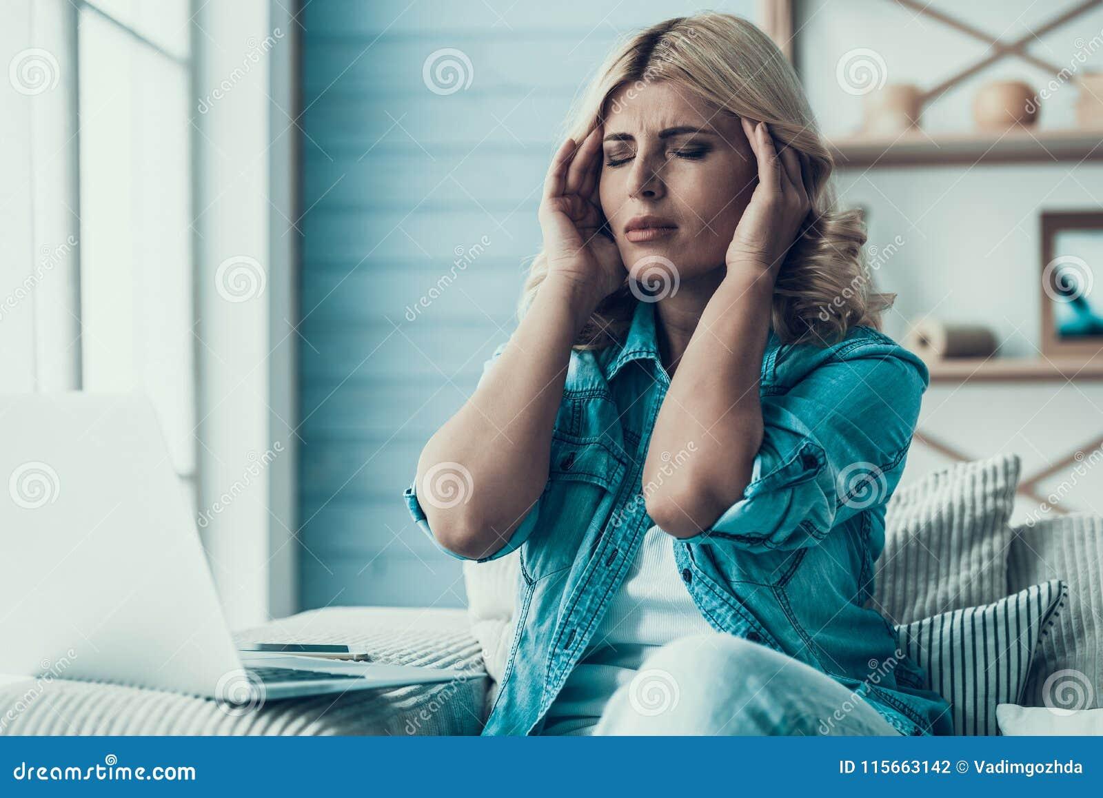 Den blonda kvinnan har huvudvärk, i att arbeta med bärbara datorn