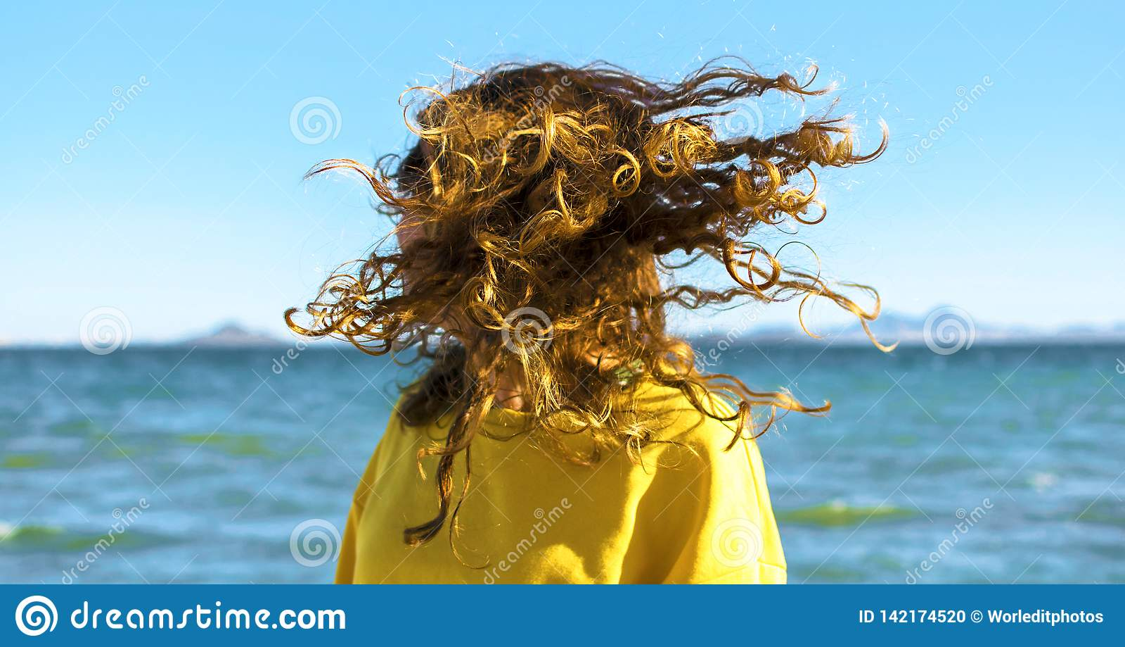 Den blonda kvinnan skakar huvudet med lockigt hår på stranden