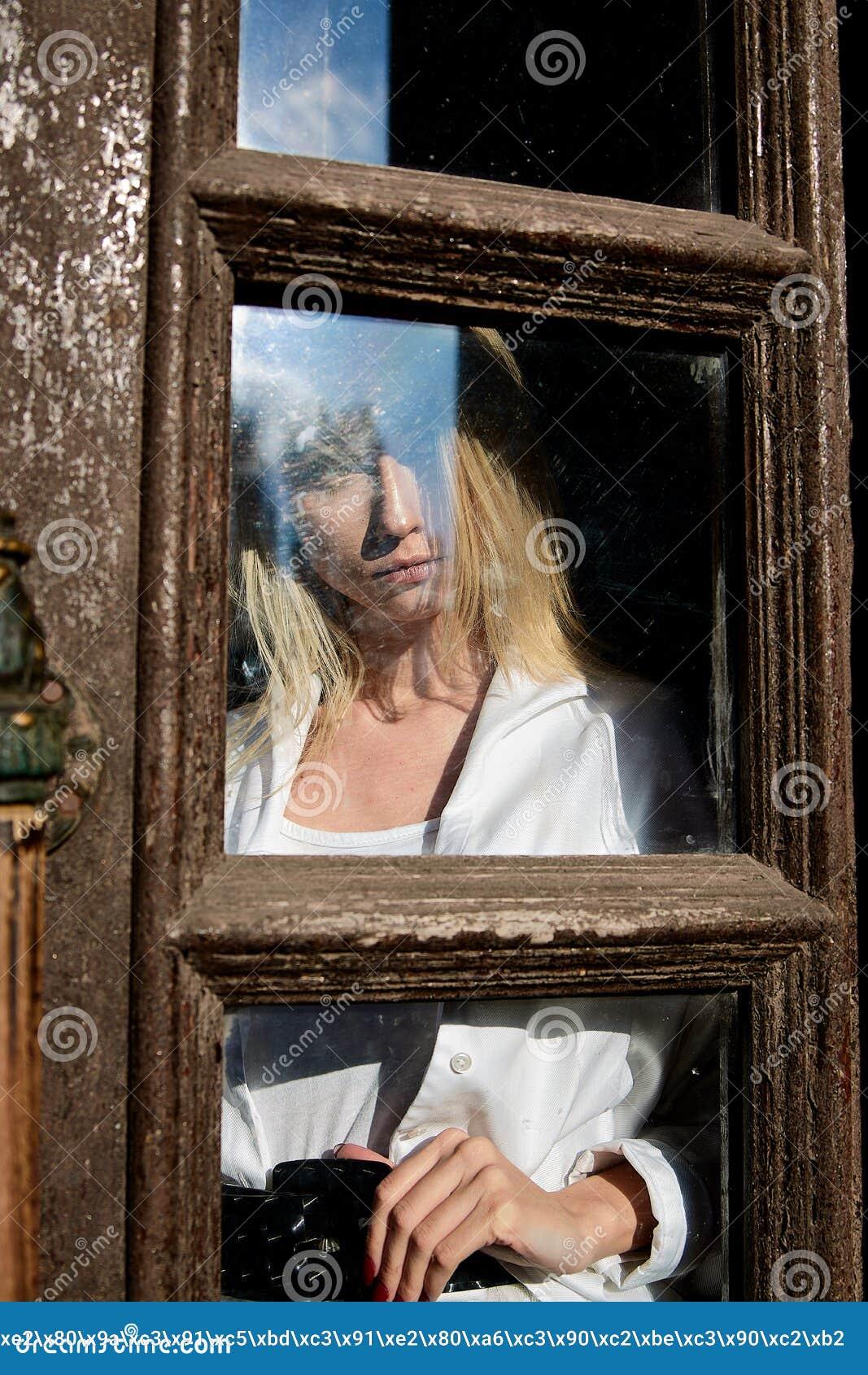 Den blonda kvinnan st?r i den gamla tr?d?rr?ppningen gammalt tr? f?r d?rr r